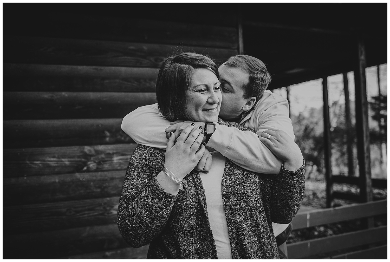 The engaged couple laugh and hug each other by the log cabin at Durant Nature Park during their engagement pictures with Rose Trail Images.