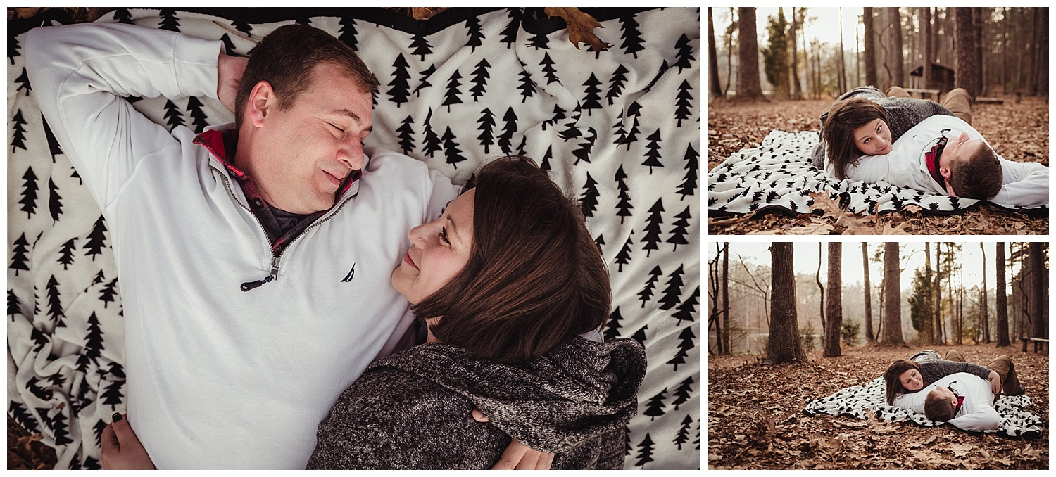 The engaged couple snuggle together on a blanket in the woods at Durant Nature Park during their engagement pictures with Rose Trail Images.