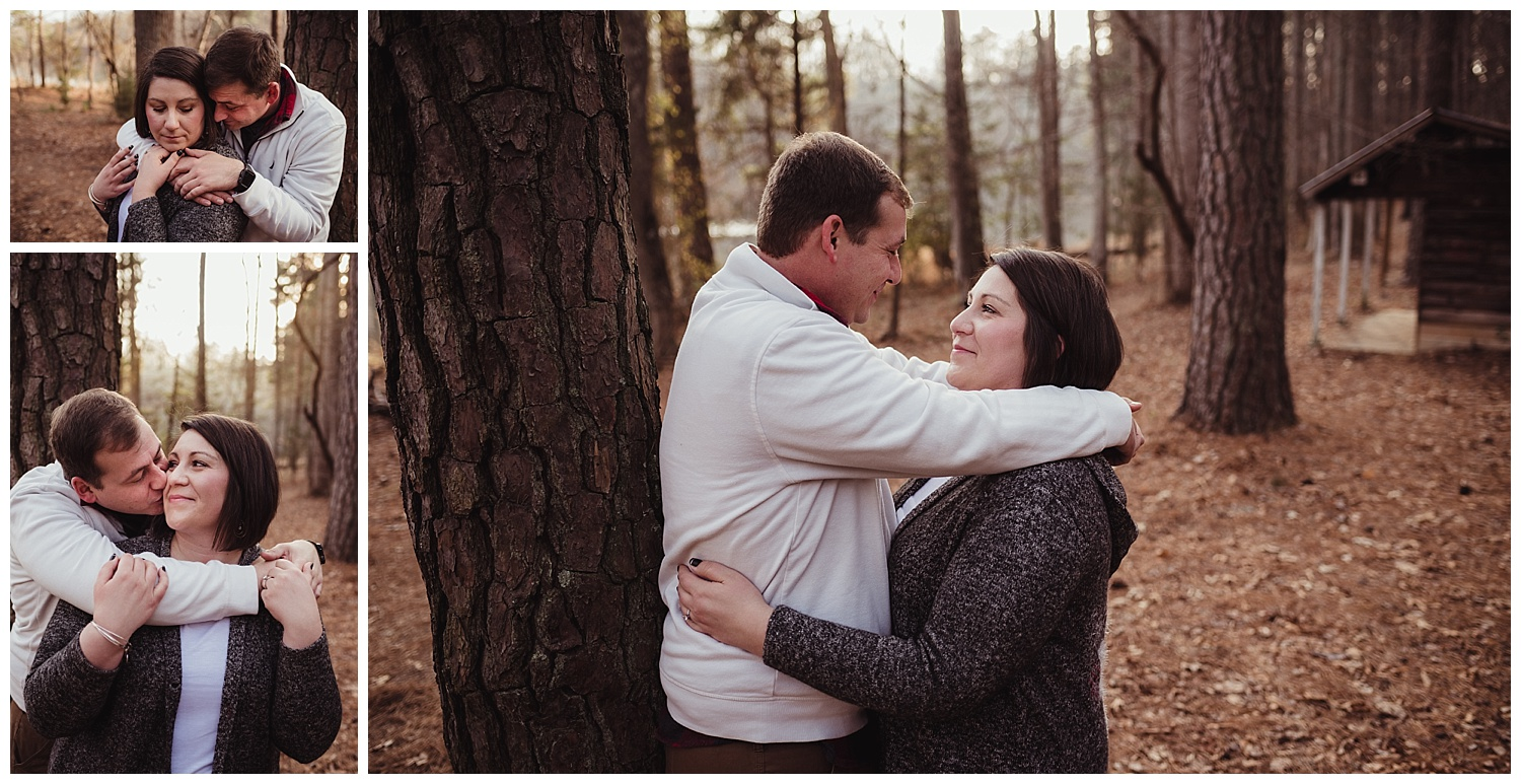 The engaged couple snuggle together in the woods at Durant Nature Park in Raleigh during their engagement session with Rose Trail Images.