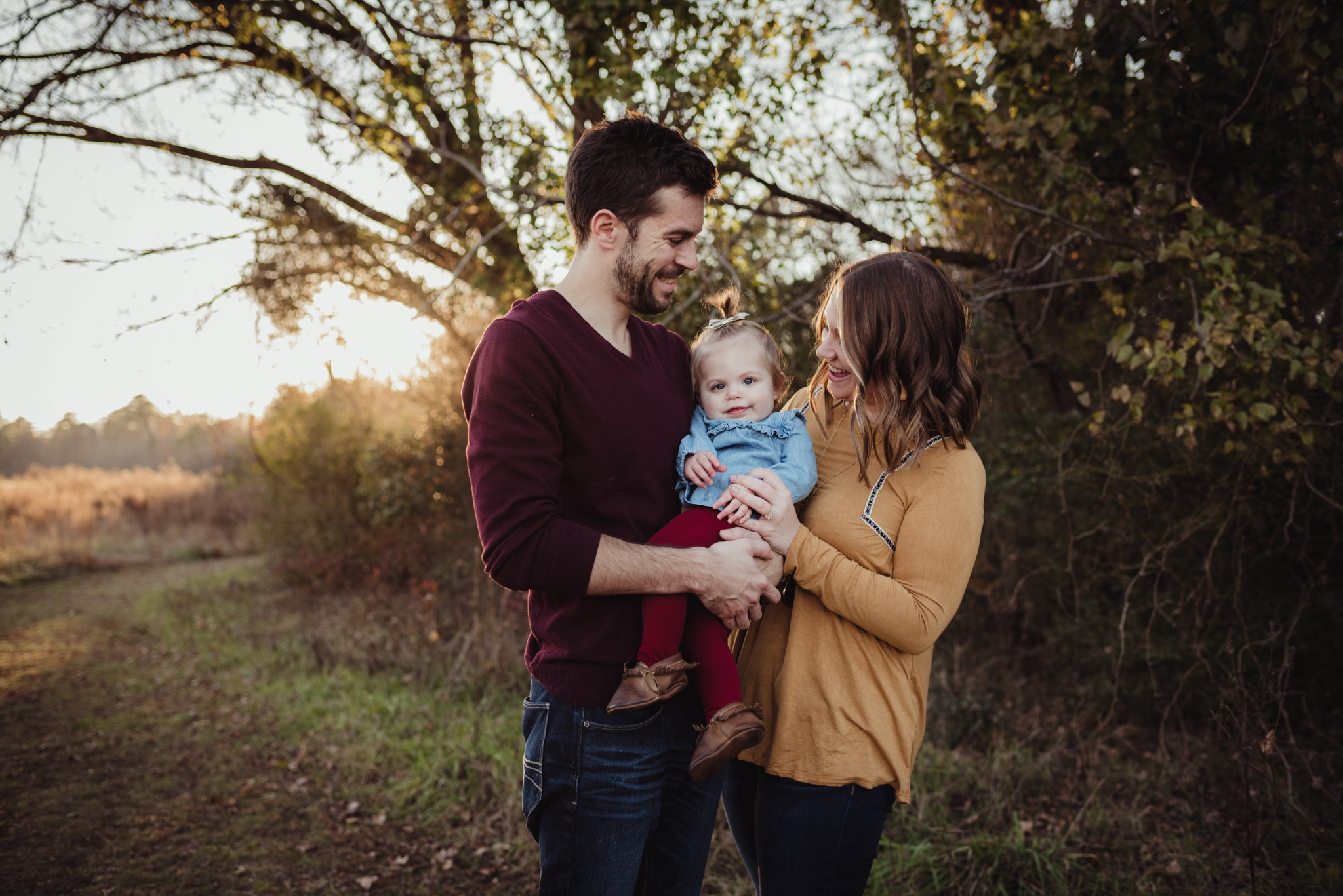 This young family of three stands with their young daughter at sunset during their family session with Rose Trail Images at Horseshoe Nature Park in Wake Forest, NC.