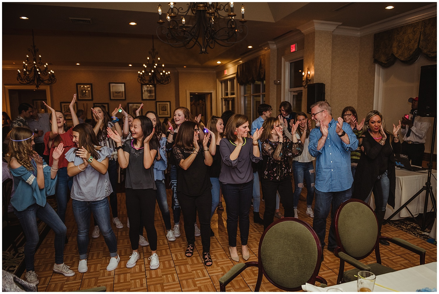 Guests dance and clap along during the mitzvah reception party with Rose Trail Images at the Brier Creek Country Club in Raleigh, NC.