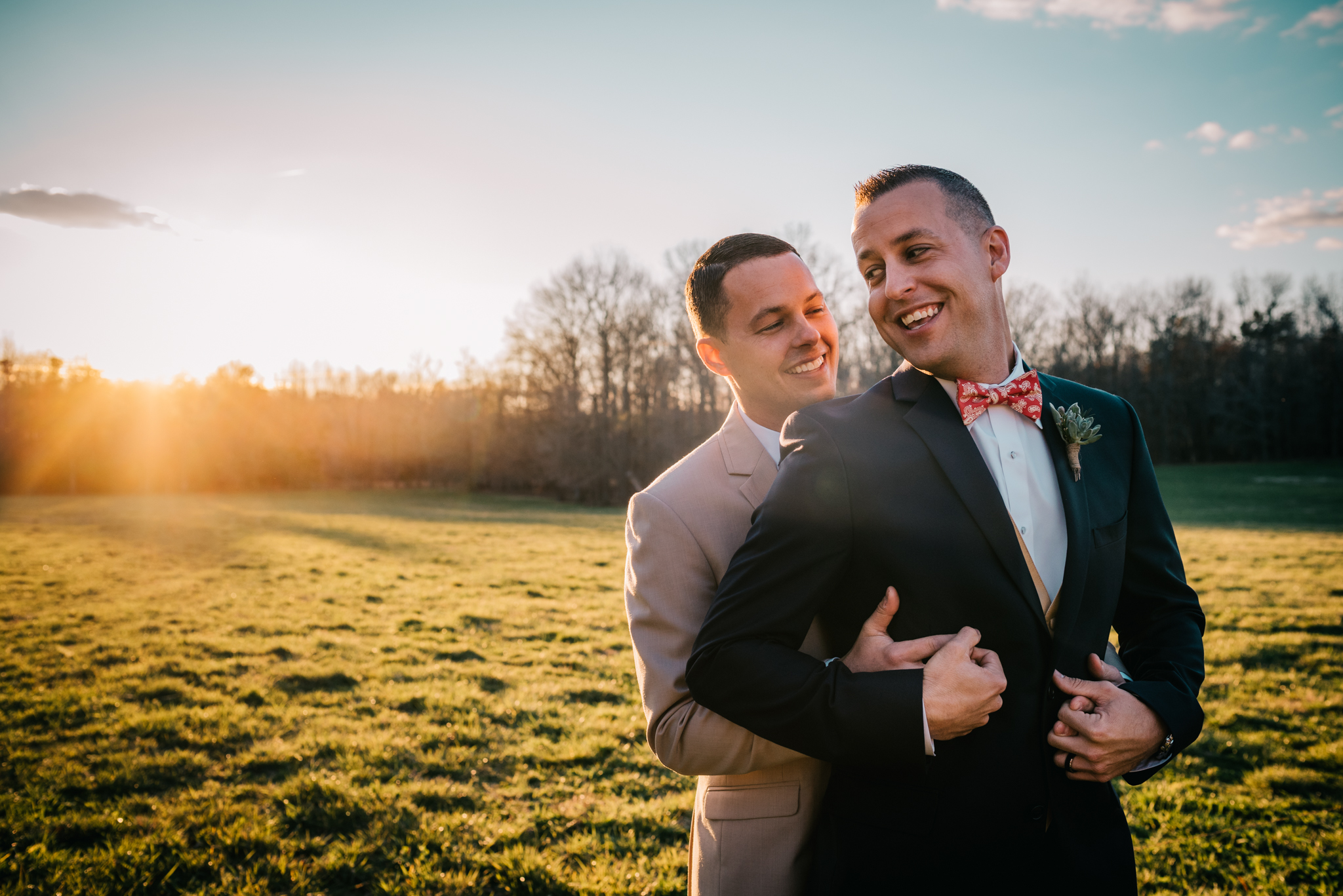 The grooms hugged at sunset during their styled engagement session with Rose Trail Images at Windy Hill Farm near Raleigh, NC.