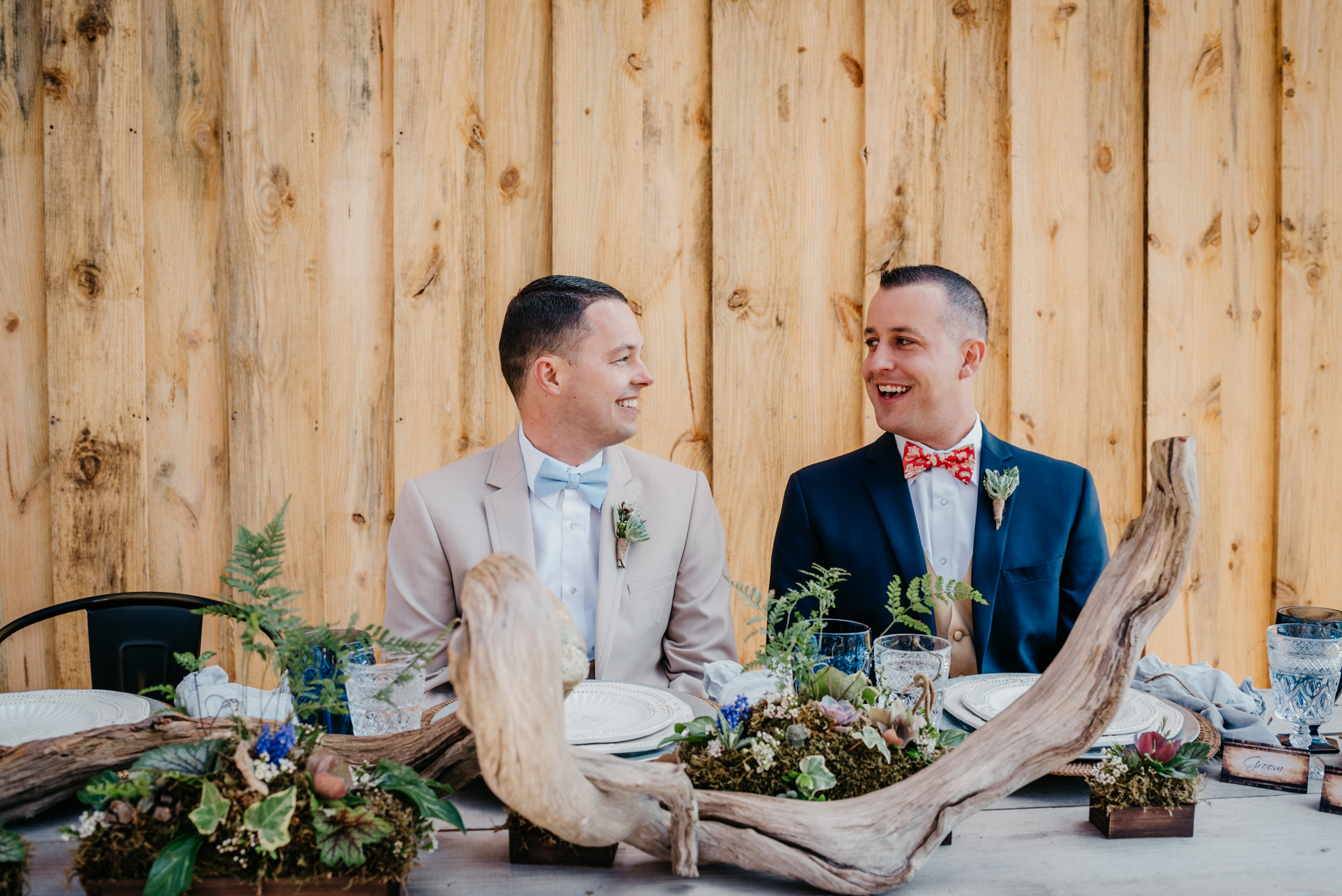 The grooms sit at the farm table during their styled engagement session with Rose Trail Images at Windy Hill Farm near Raleigh, NC.