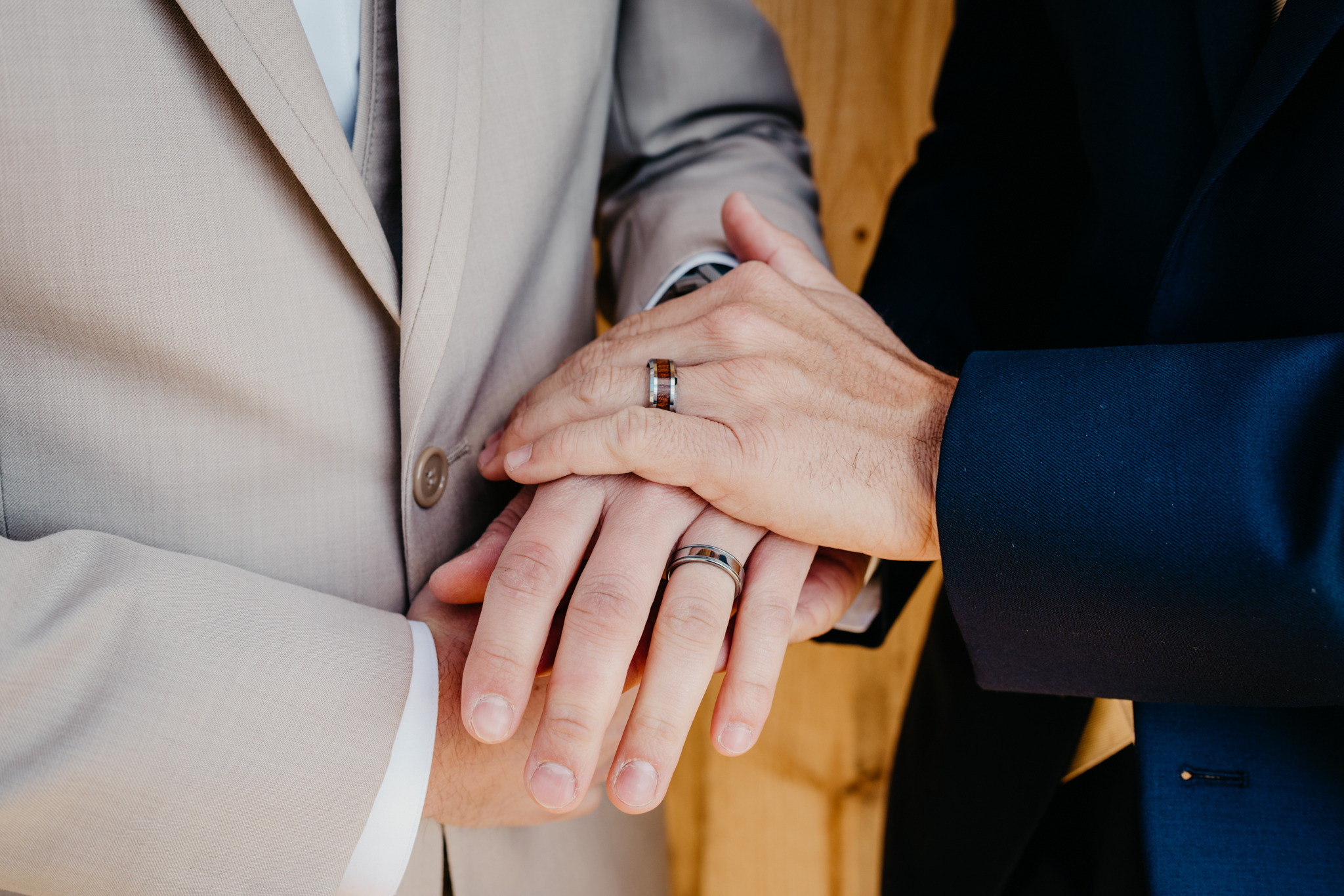A close up of the grooms hands with their personalized wedding bands at their styled engagement session with Rose Trail Images at Windy Hill Farm near Raleigh, NC.