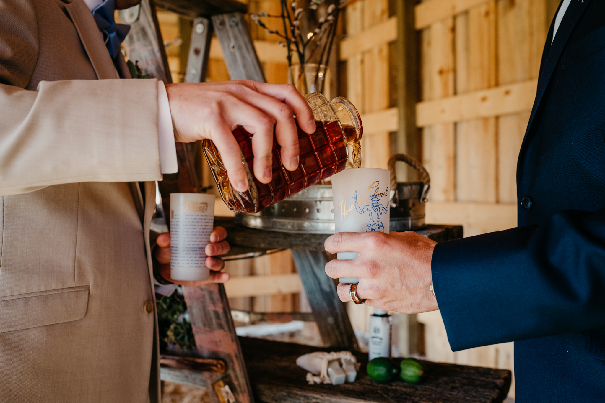 The grooms pour themselves a whiskey sour drink during their styled engagement session with Rose Trail Images at Windy Hill Farm near Raleigh, NC.