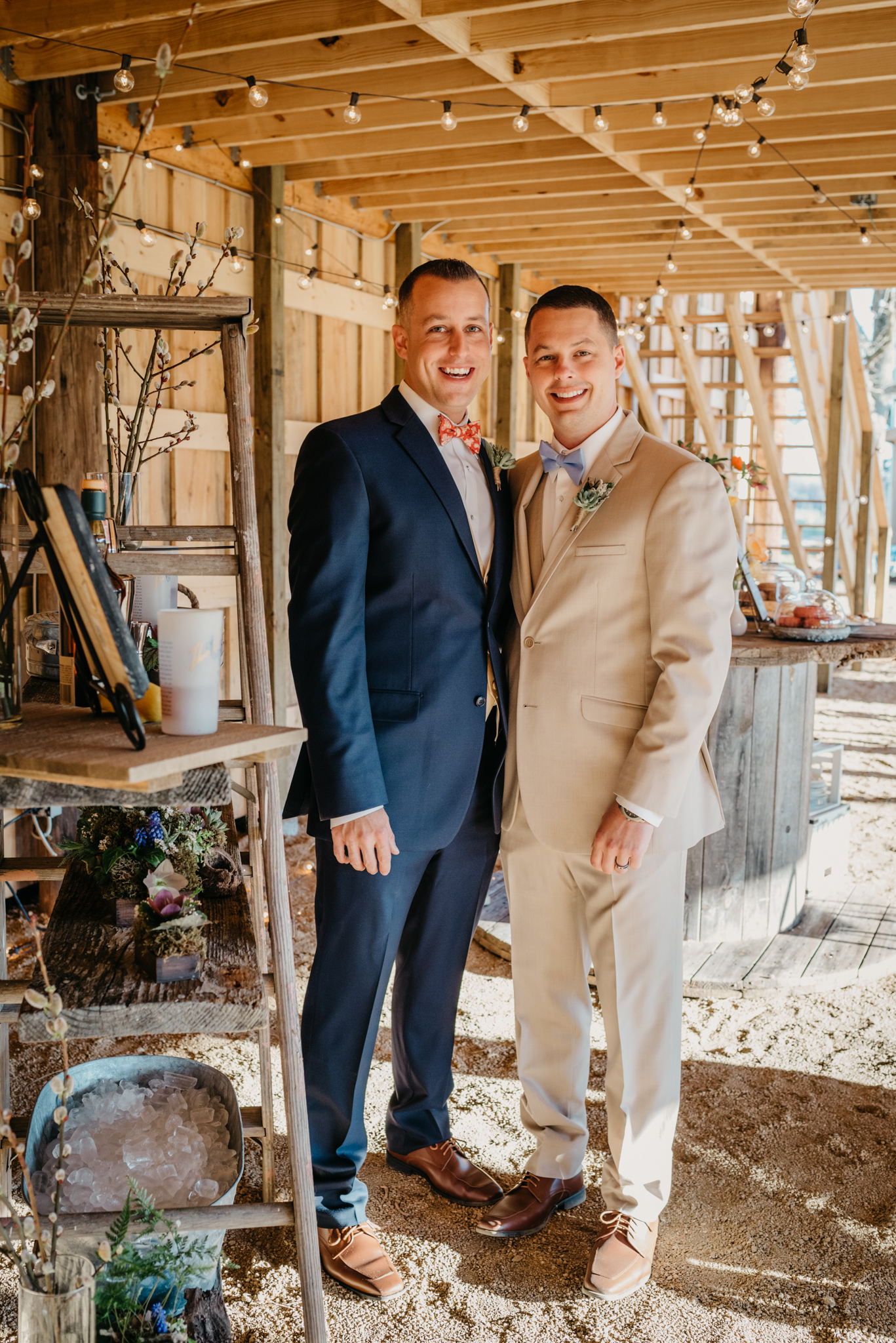 The grooms pose in their rustic farm reception decor during their styled engagement session with Rose Trail Images at Windy Hill Farm near Raleigh, NC.