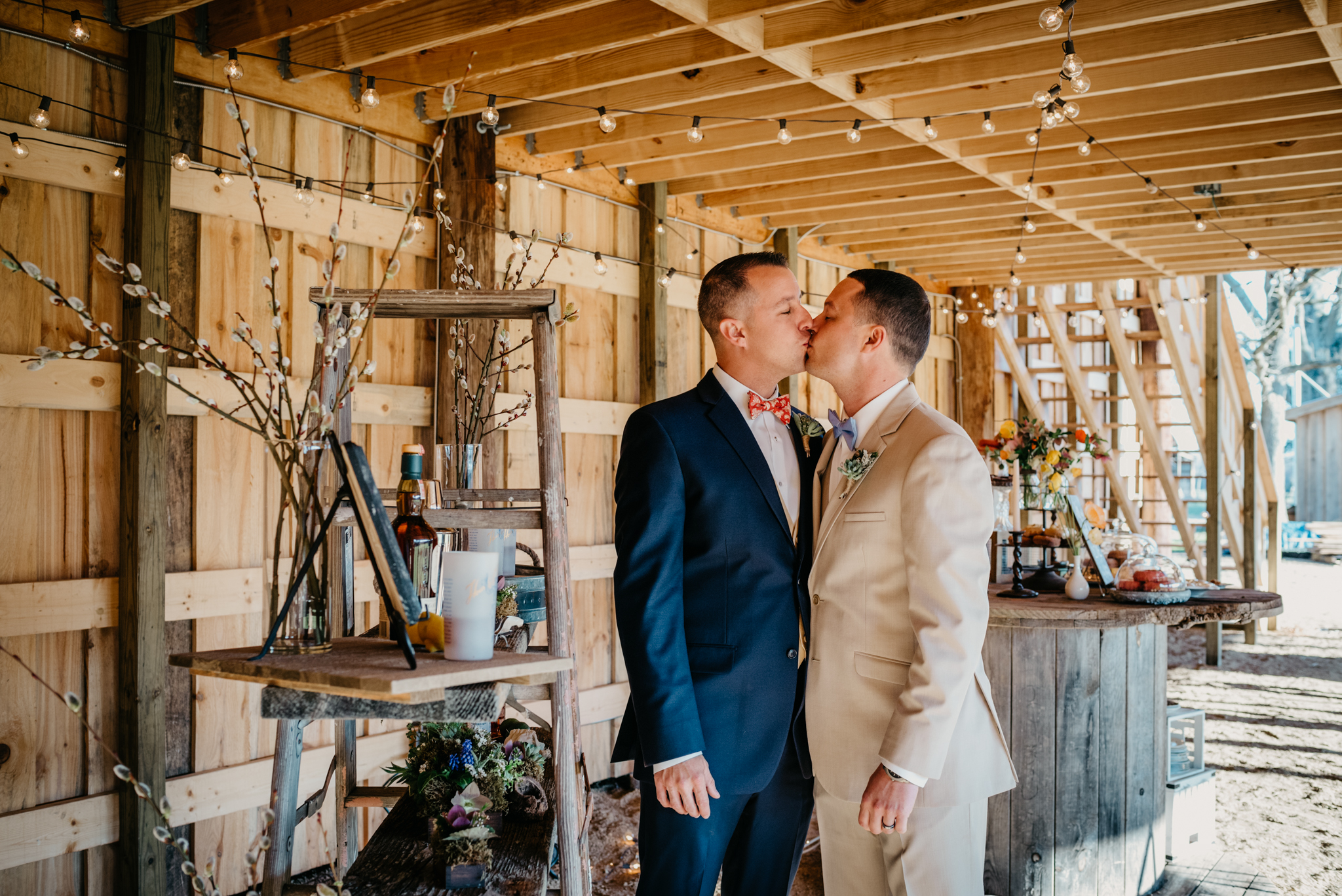 The grooms steal a kiss in the middle of the rustic farm reception decor during their styled engagement session with Rose Trail Images at Windy Hill Farm near Raleigh, NC.