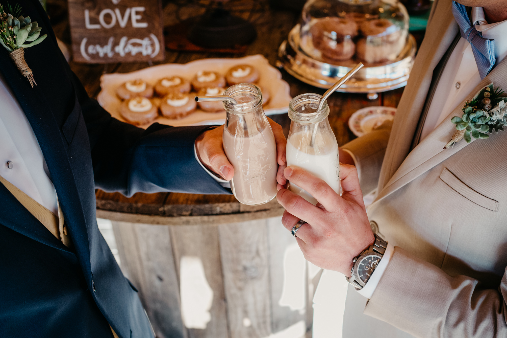The grooms toasted with chocolate and regular milk, along with their donuts, at the rustic farm styled engagement session with Rose Trail Images at Windy Hill Farm near Raleigh, NC.