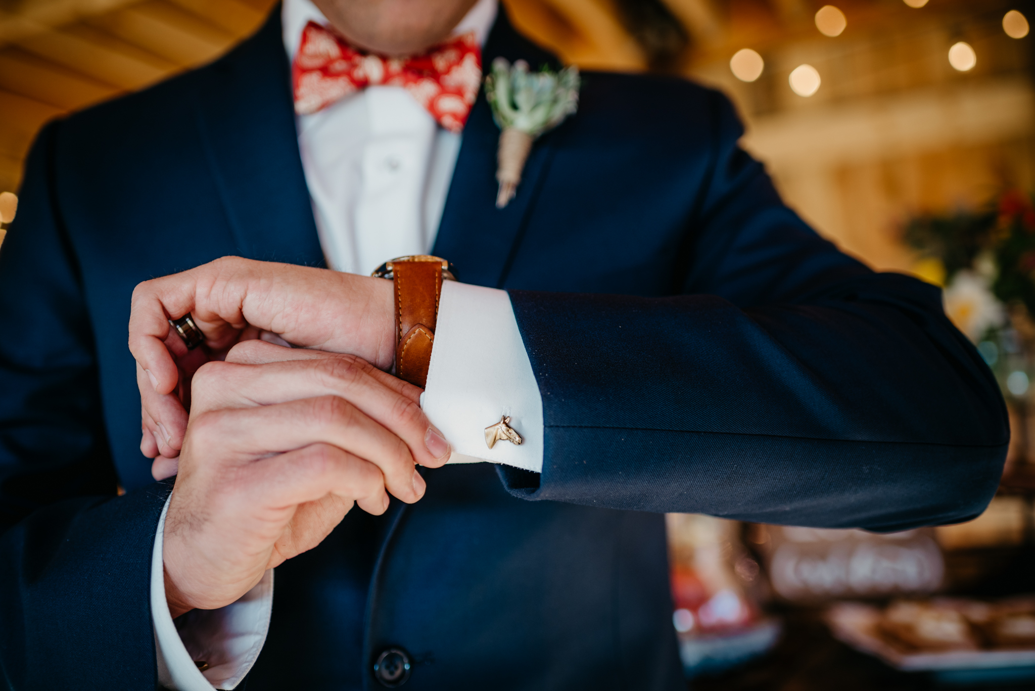 A close up of one of the grooms' horse head cufflinks at their styled engagement session with Rose Trail Images at Windy Hill Farm near Raleigh, NC.