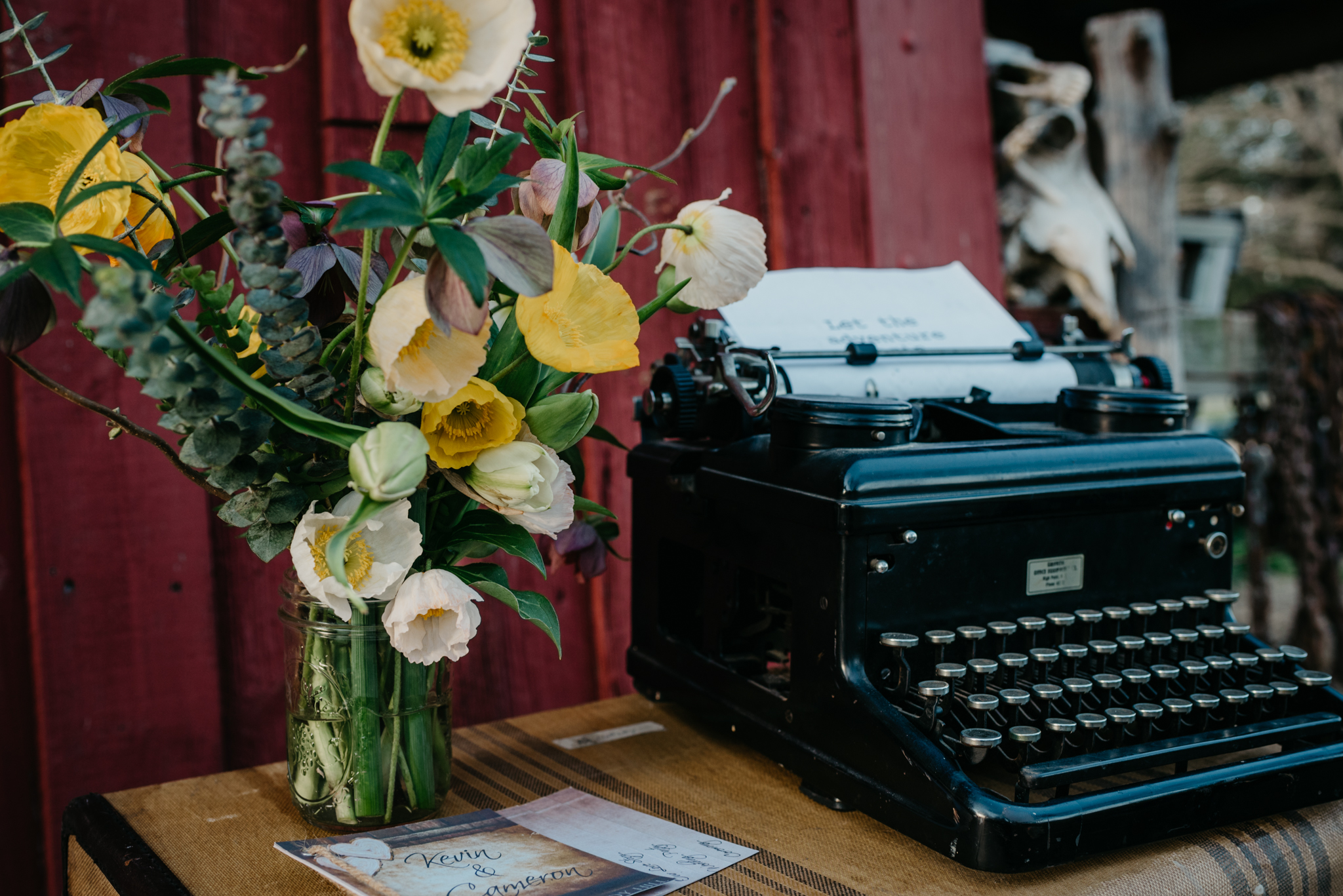 The typewriter, flowers, and invitations were setup outside in the sunset at the rustic styled engagement session with Rose Trail Images at Windy Hill Farm near Raleigh, NC.