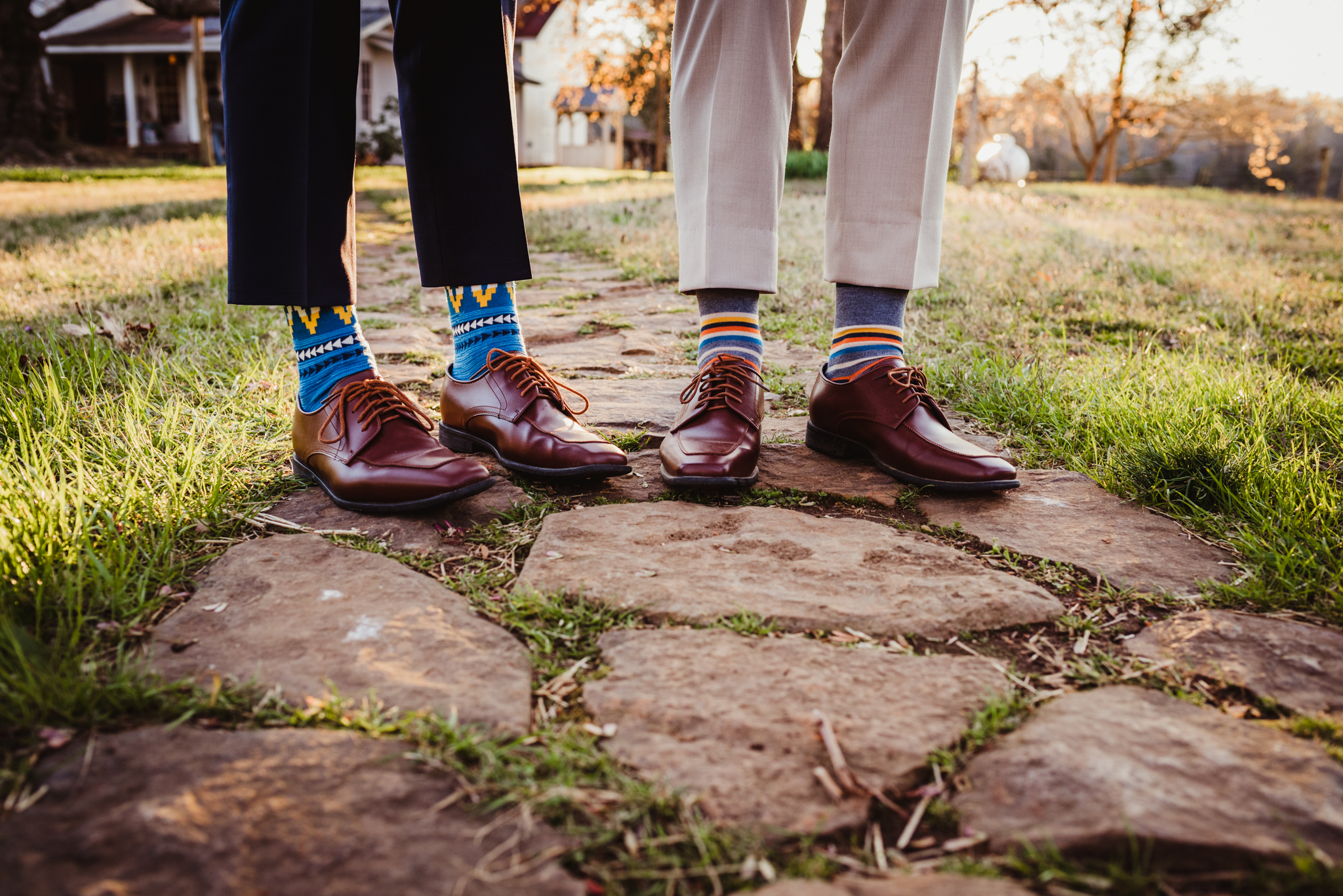 The grooms show off their patterned socks on the stone pathway at the rustic styled engagement session with Rose Trail Images at Windy Hill Farm near Raleigh, NC.