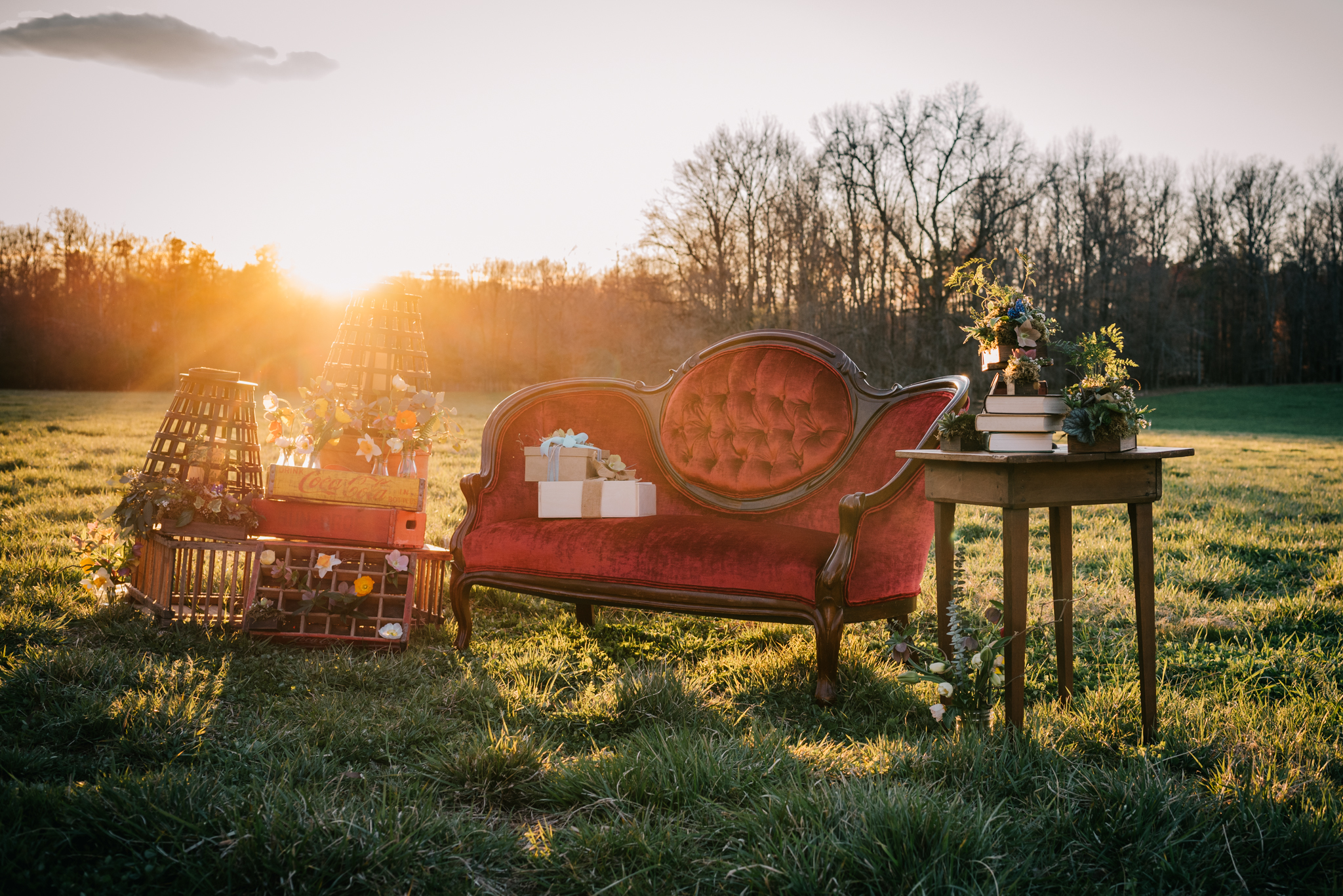 The red couch is adorned with flowers, gifts, and rustic decor while in the sunset at the rustic styled engagement session with Rose Trail Images at Windy Hill Farm near Raleigh, NC.