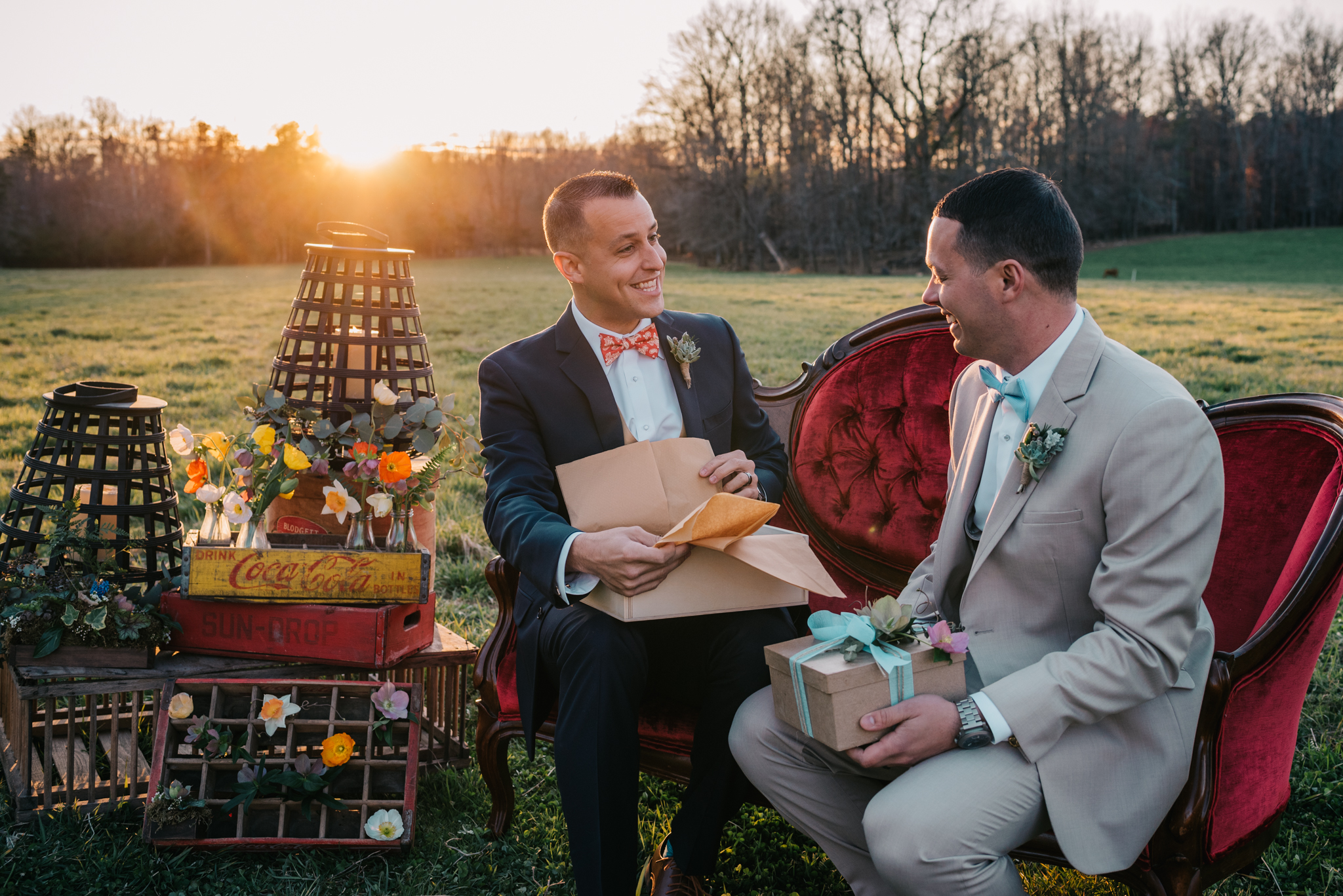The grooms sit on the red couch in the sunset and give each other gifts during the rustic styled engagement session with Rose Trail Images at Windy Hill Farm near Raleigh, NC.
