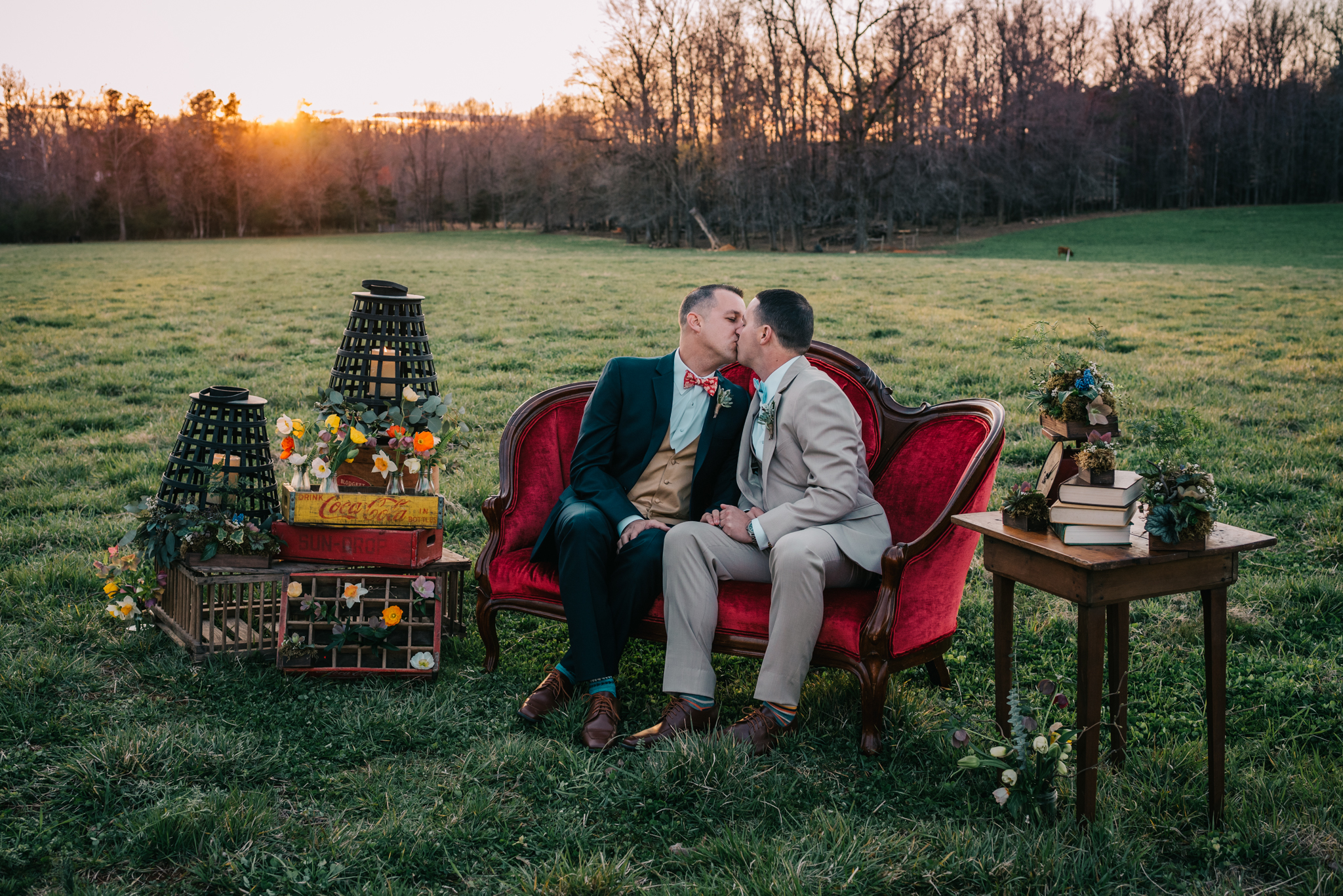 The grooms kiss on the red couch in the sunset during the rustic styled engagement session with Rose Trail Images at Windy Hill Farm near Raleigh, NC.
