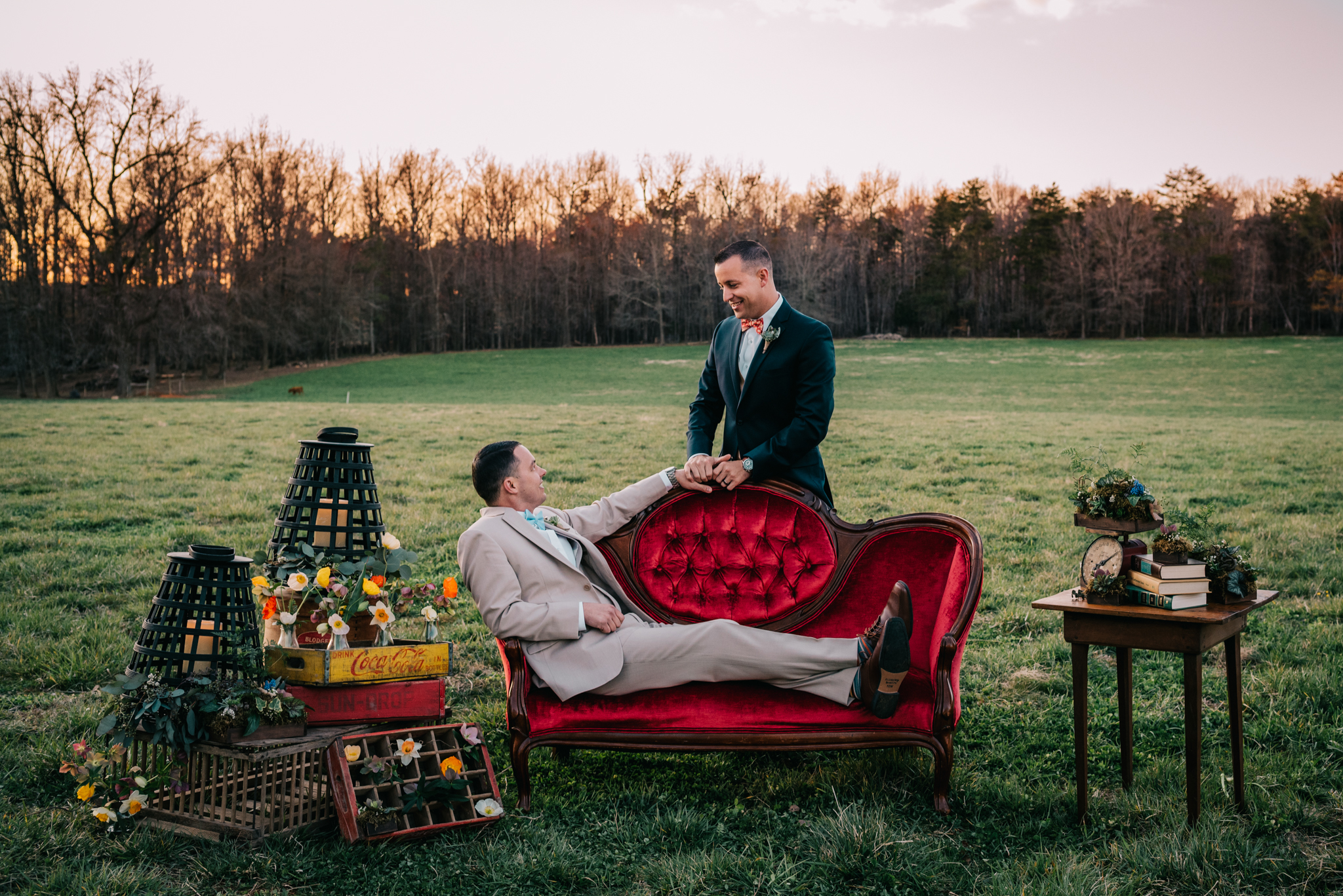 The grooms pose at the red couch with the flowers and rustic decor during sunset at the farm styled engagement session with Rose Trail Images at Windy Hill Farm near Raleigh, NC.