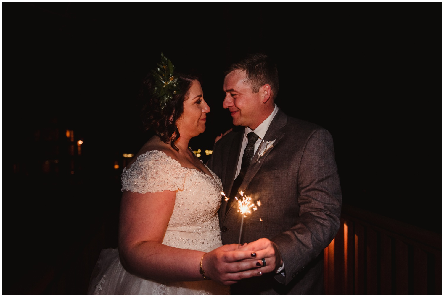 The bride and groom look at each other while holding a sparkler on their wedding day at the Barn at Valhalla in Chapel Hill, taken by Rose Trail Images.