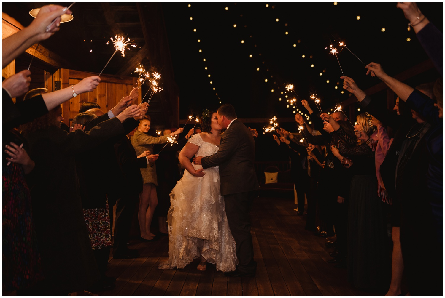 The bride and groom kiss during their sparkler exit on their wedding day at the Barn at Valhalla in Chapel Hill, taken by Rose Trail Images.