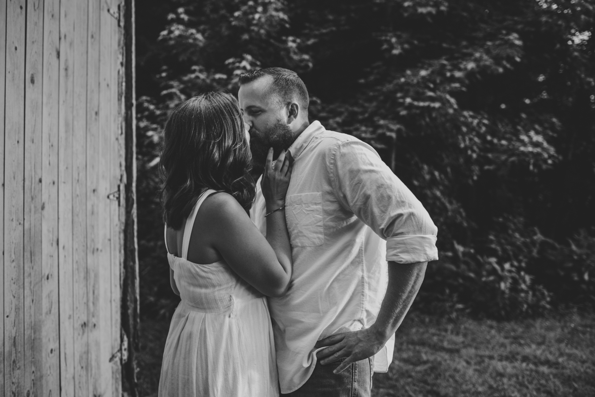 The couple share a kiss by the barn for their engagement pictures with Rose Trail Images at Horseshoe Park in Wake Forest, North Carolina.