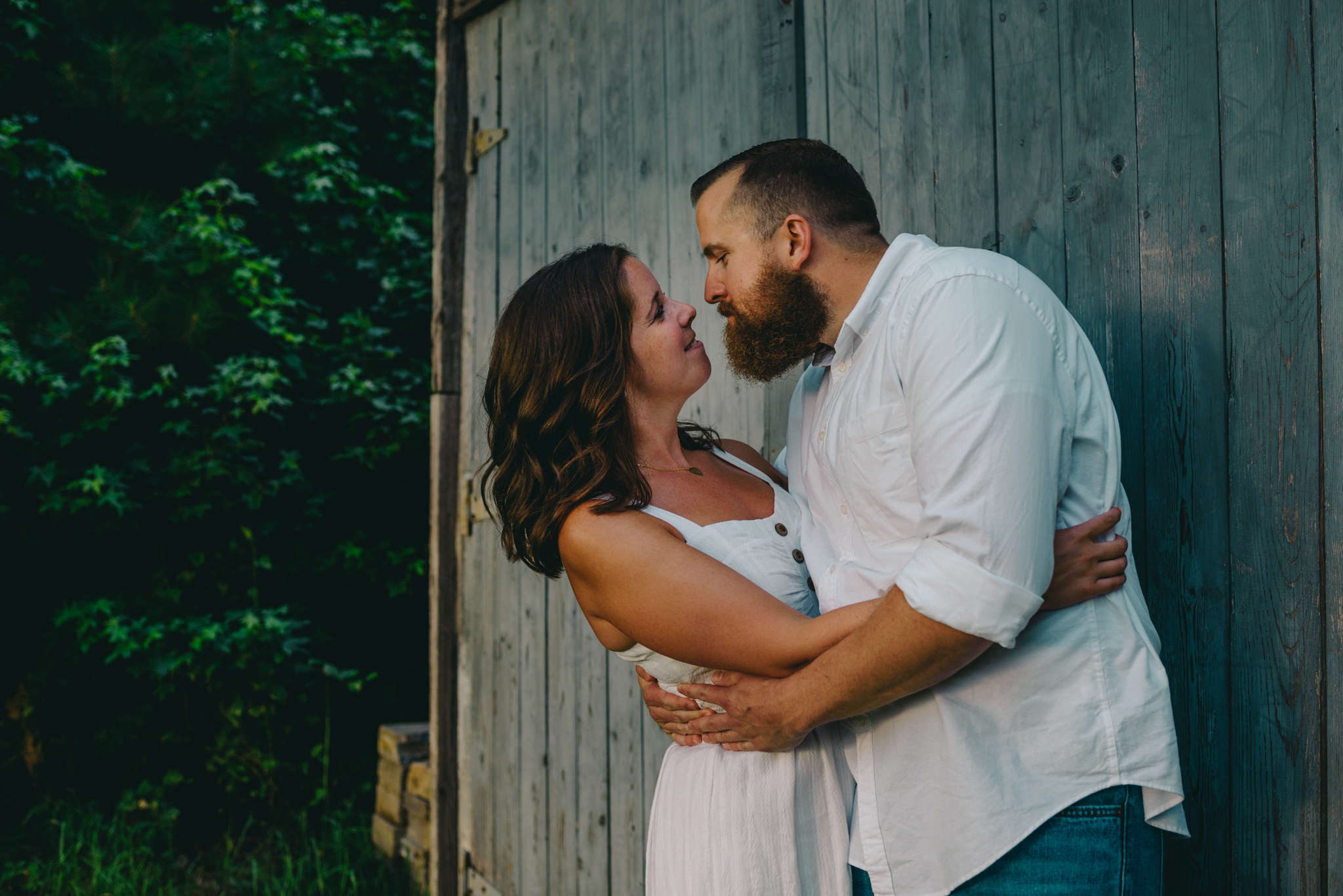 The couple get ready for a kiss by the barn at sunset for their engagement pictures with Rose Trail Images at Horseshoe Park in Wake Forest, North Carolina.