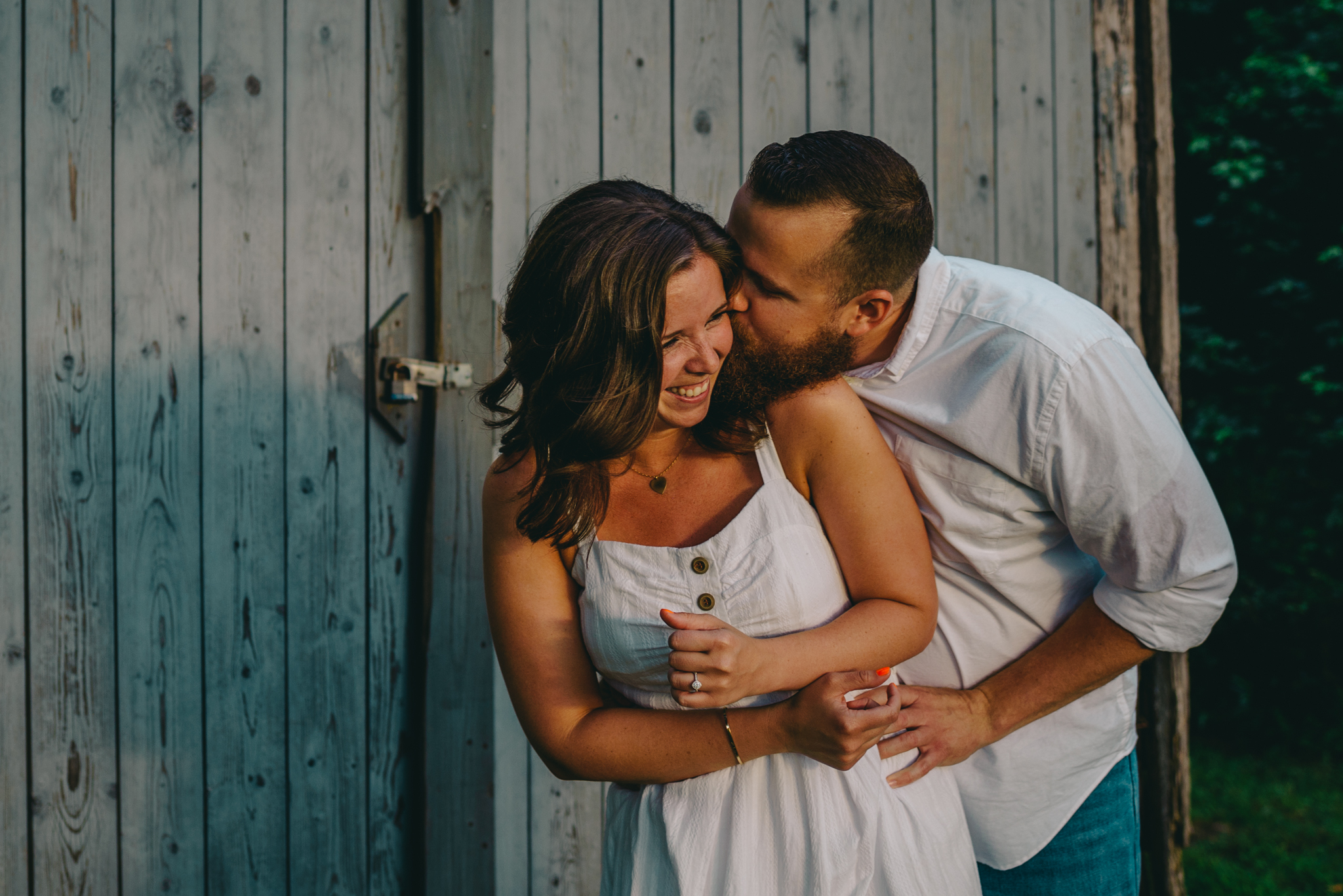 The couple laugh together by the barn at sunset during their engagement pictures with Rose Trail Images at Horseshoe Park in Wake Forest, North Carolina.