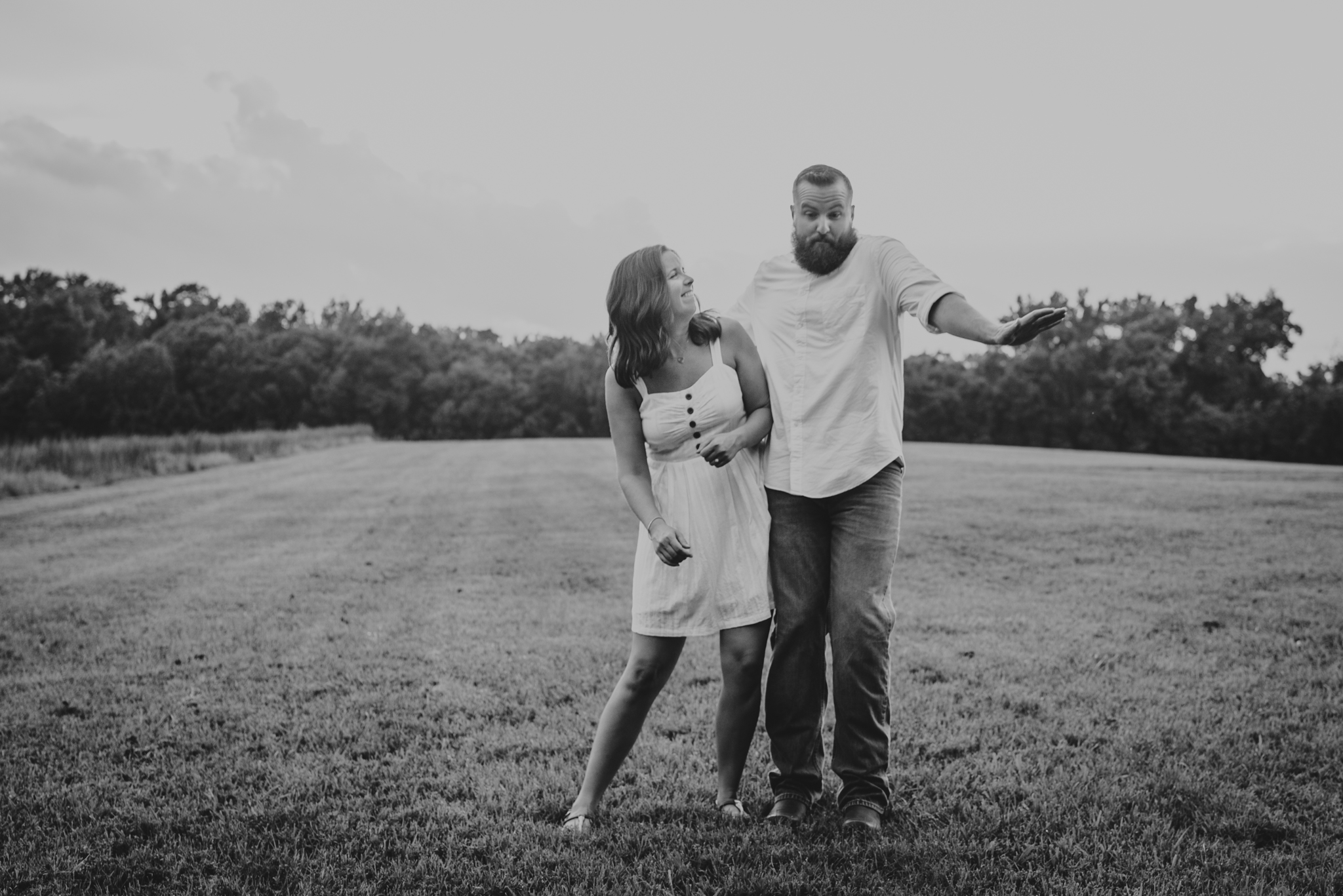 The couple hip check each other during their engagement pictures with Rose Trail Images at Horseshoe Park in Wake Forest, North Carolina.
