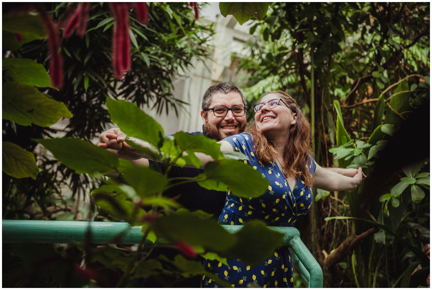 """The couple act out the """"King of the World"""" scene from the Titanic during their engagement photo session with Rose Trail Images at the Butterfly House in Durham."""