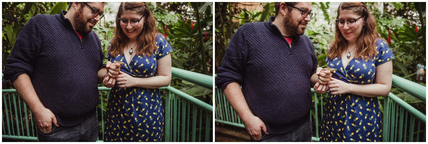 A butterfly lands on the couples' hands during their engagement photo session with Rose Trail Images at the Butterfly House in Durham.