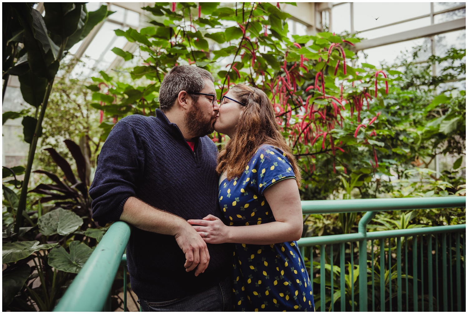 The couple steal a kiss in the Butterfly House during their engagement photo session with Rose Trail Images in Durham, NC.