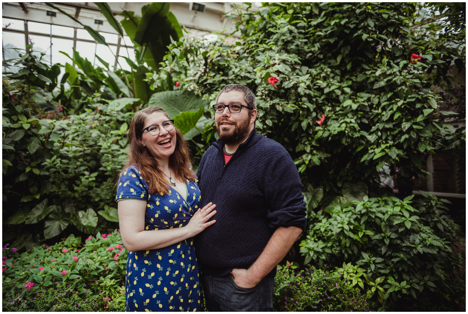 The couple laugh together while in the Butterfly House during their engagement photo session with Rose Trail Images in Durham, NC.
