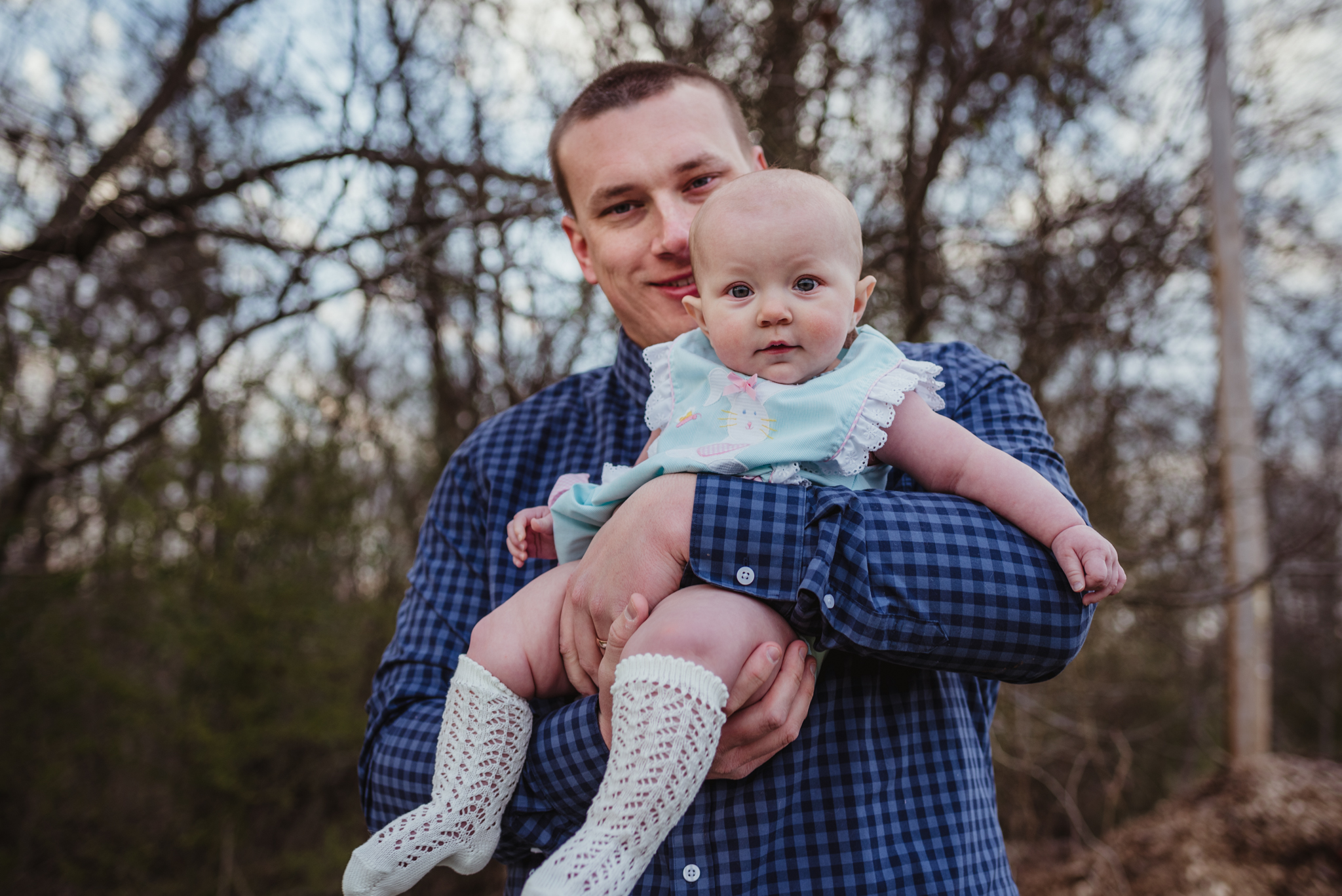 A dad plays with his 9-month old during their family photos with Rose Trail Images at Horseshoe Farm Park in Wake Forest, NC.