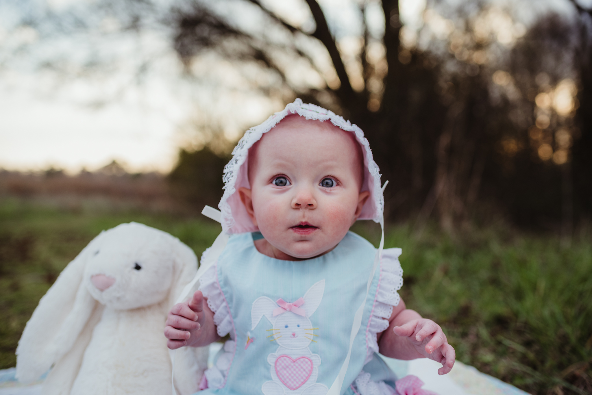 A 9-month old sits in her easter bonnet during their family photos with Rose Trail Images at Horseshoe Farm Park in Wake Forest, NC.