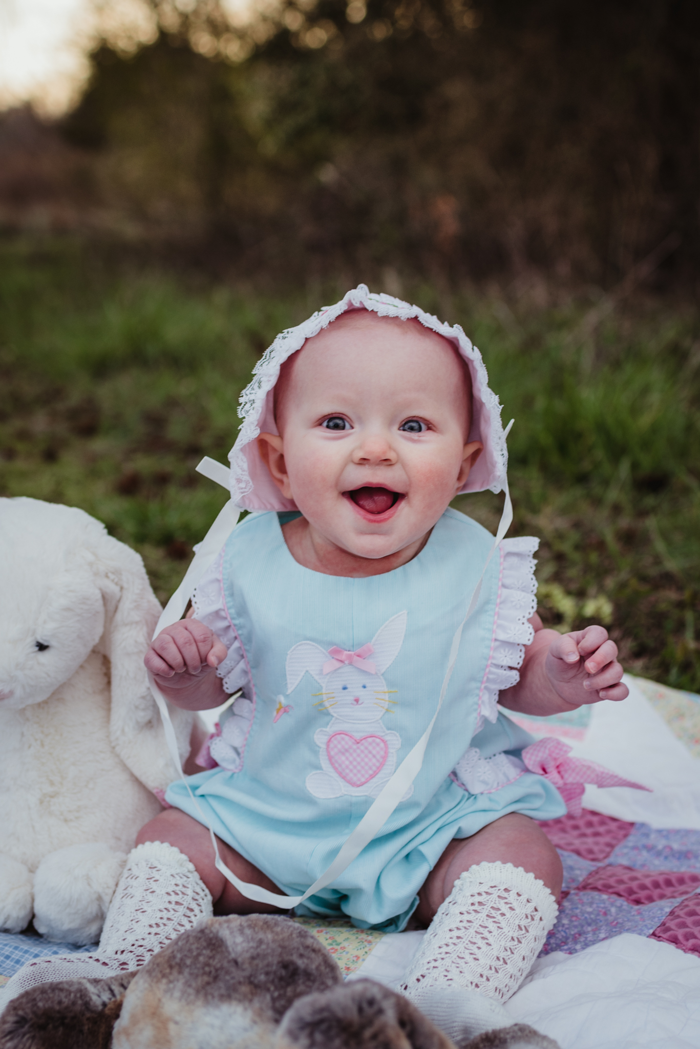 A 9-month old sits in her easter bonnet and laughs during their family photos with Rose Trail Images at Horseshoe Farm Park in Wake Forest, NC.