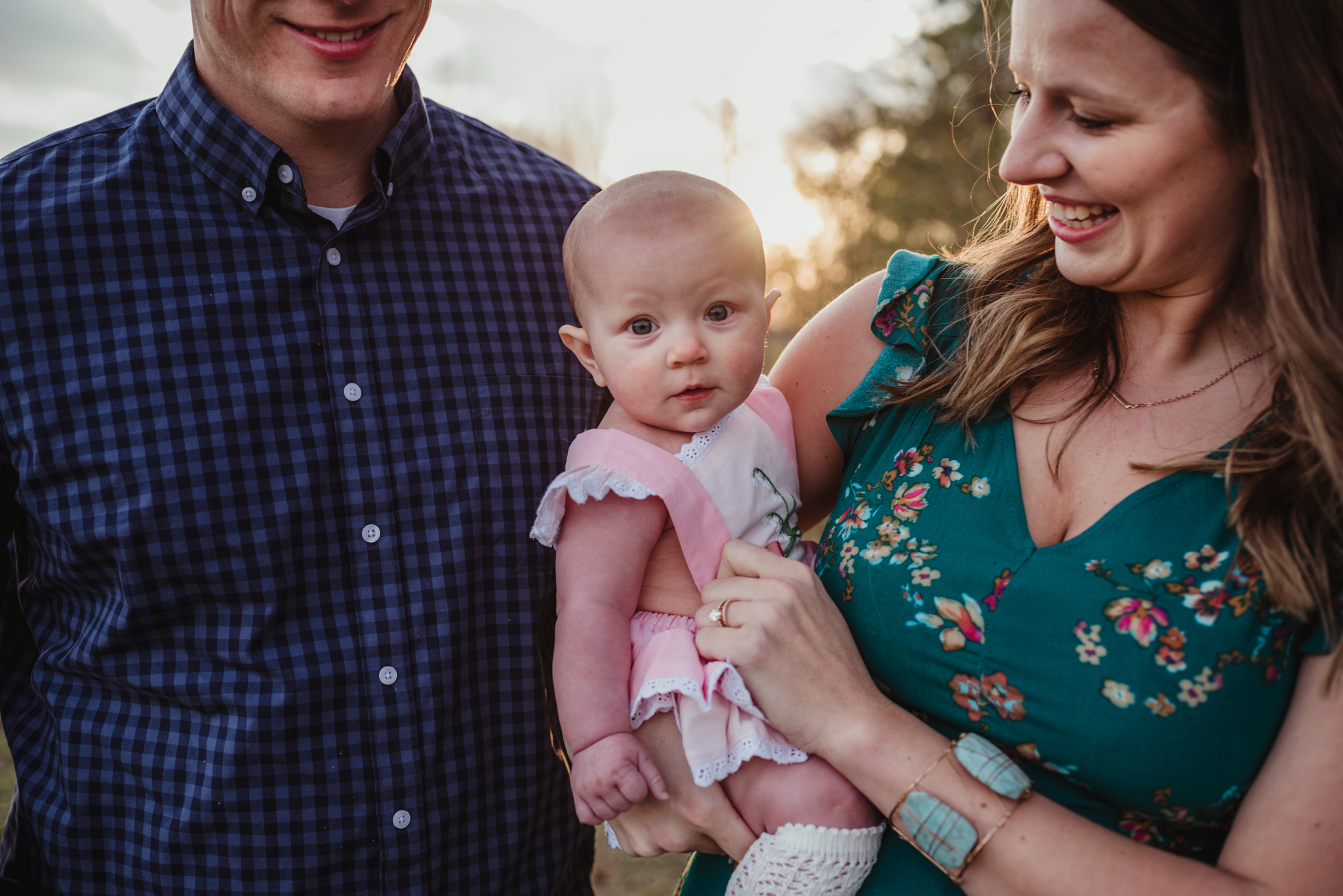 The nine month old poses with her family at sunset during their family photos with Rose Trail Images at Horseshoe Farm Park in Wake Forest, NC.