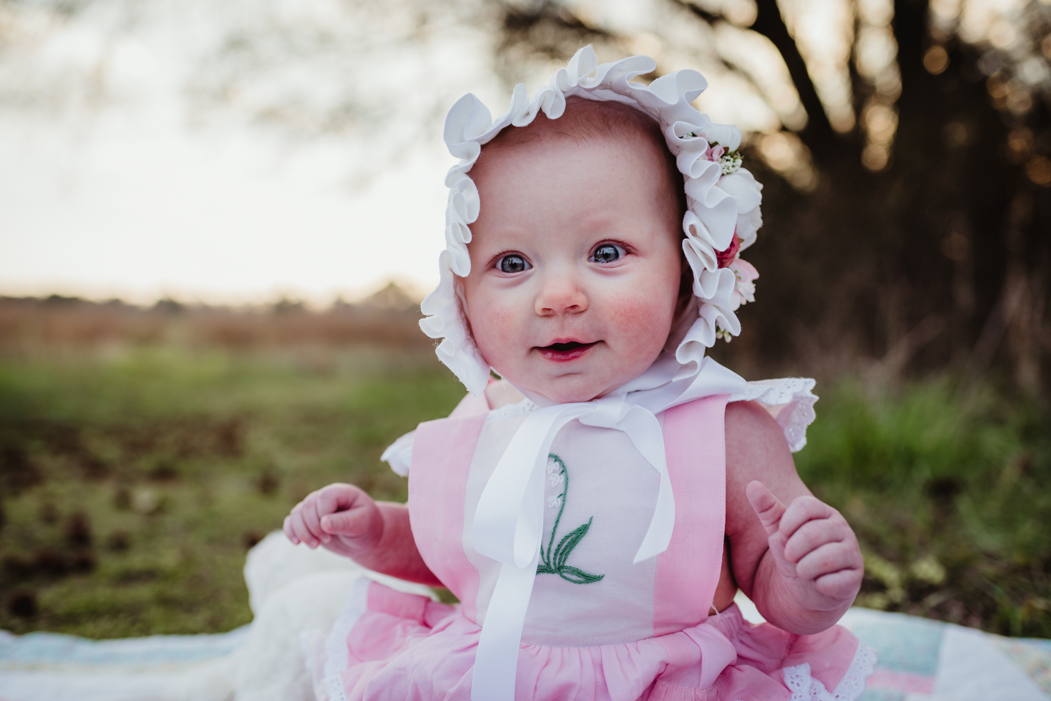 The baby smiles for the camera with her Easter bonnet on at sunset during their family photos with Rose Trail Images at Horseshoe Farm Park in Wake Forest, NC.