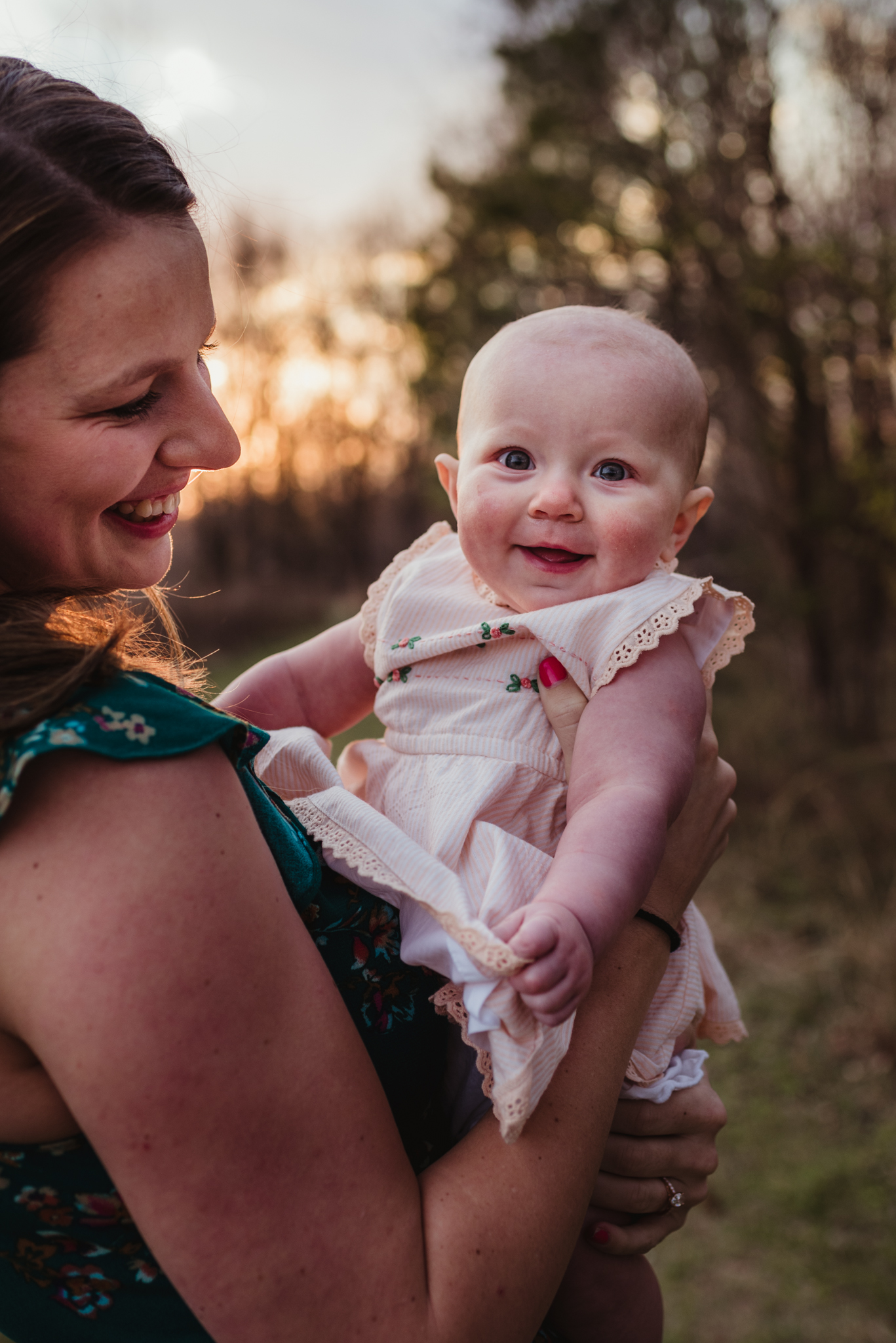 The baby smiles with her mom at sunset during their family photos with Rose Trail Images at Horseshoe Farm Park in Wake Forest, NC.