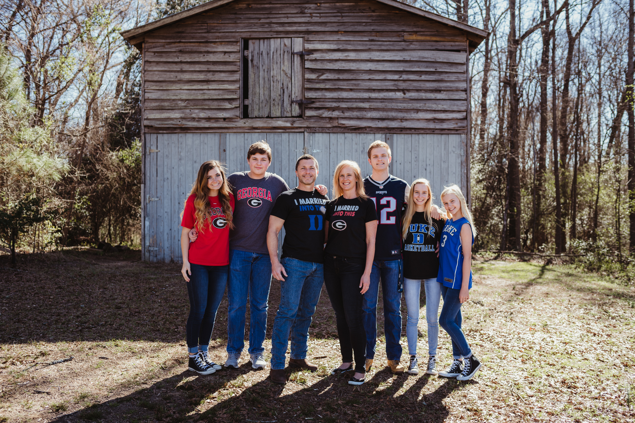 The couple stand together with their family during their engagement session with Rose Trail Images at a barn in Wake Forest, NC.