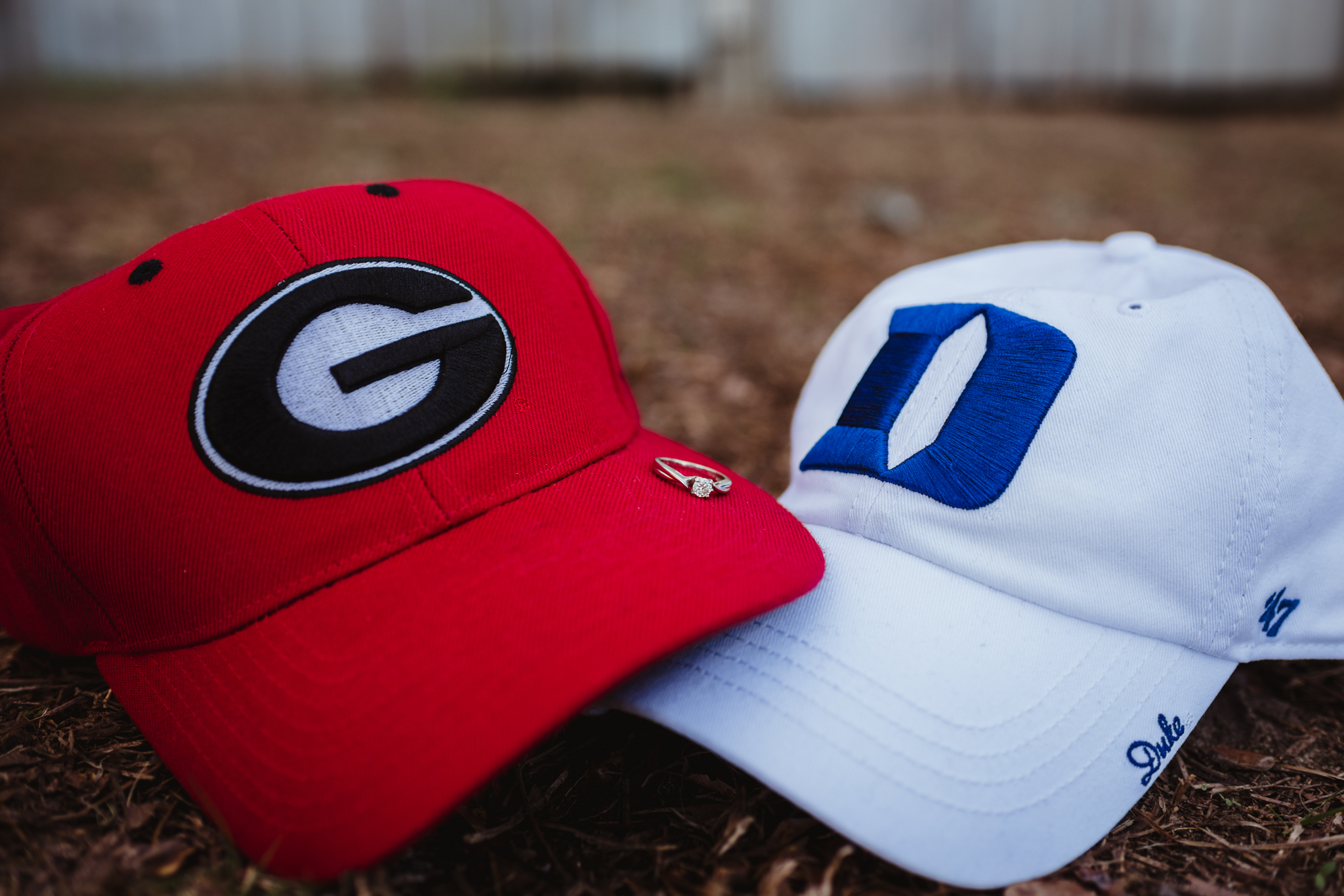 Her engagement ring was carefully placed on the Georgia Bulldogs and Duke BlueDevils hats during their engagement session with Rose Trail Images at a barn in Wake Forest, NC.