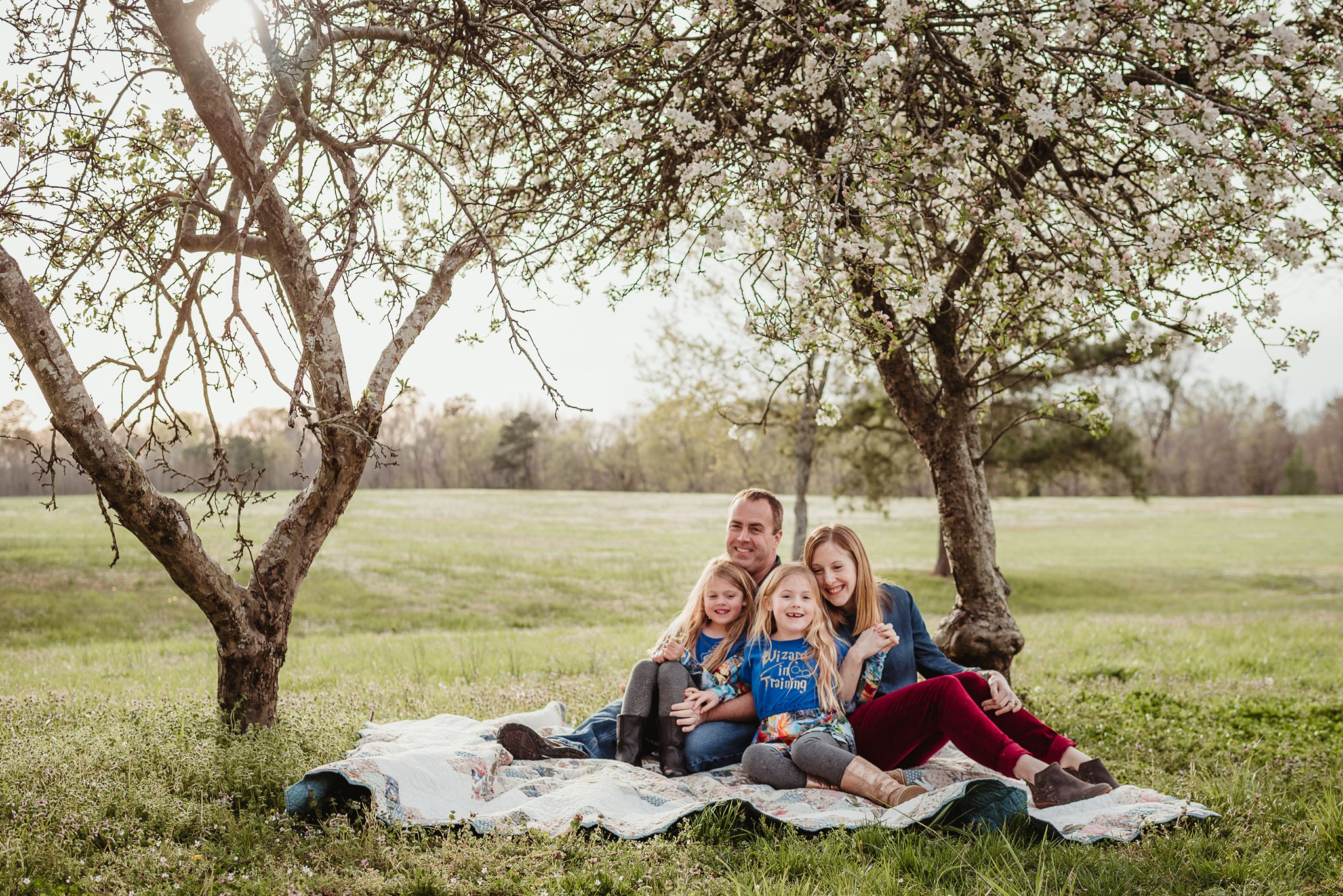 This family of four sat on their quilt and posed for Rose Trail Images during their family photo session in Wake Forest, North Carolina.