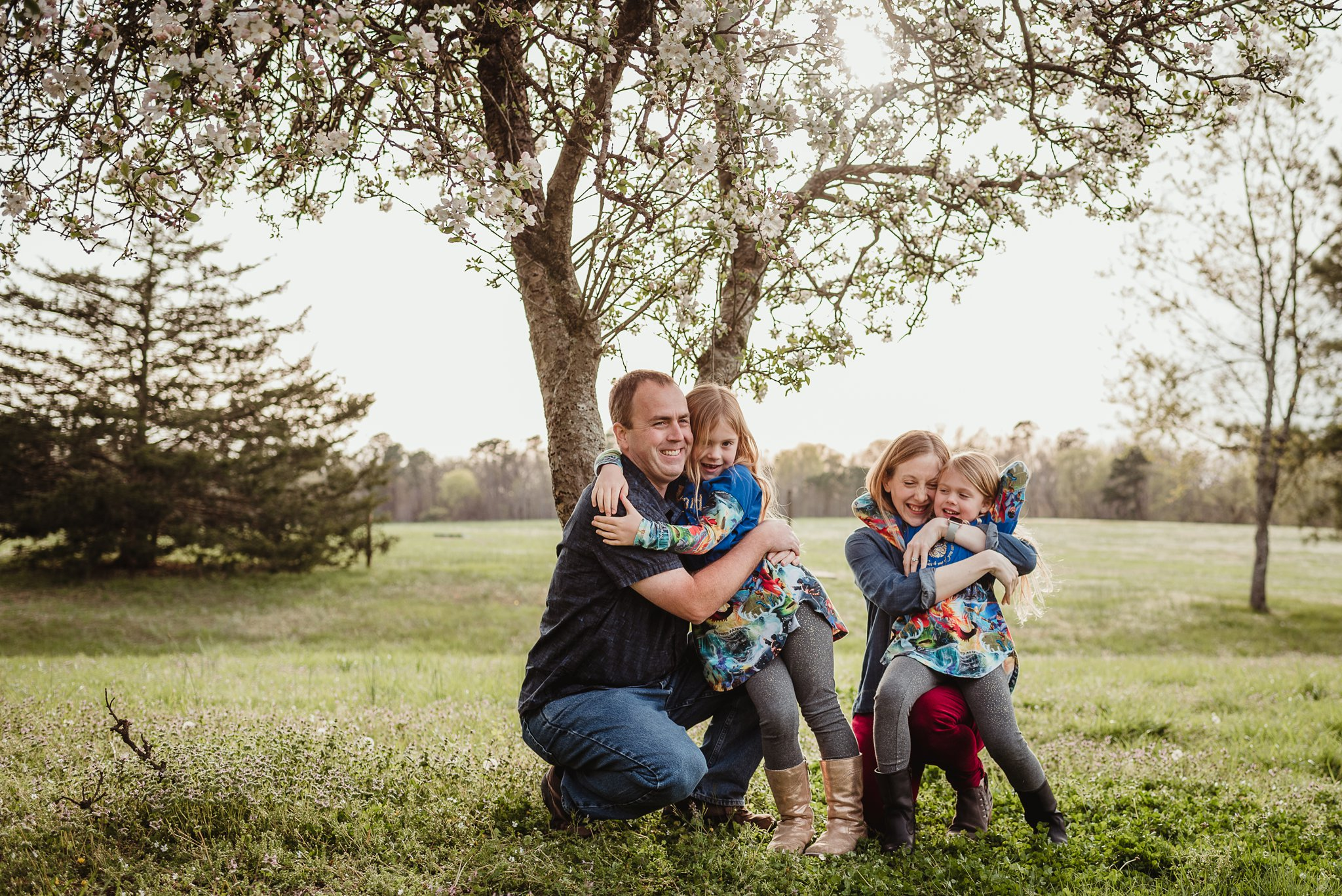 The daughters hug their parents during their family photo session with Rose Trail Images in Wake Forest, North Carolina.