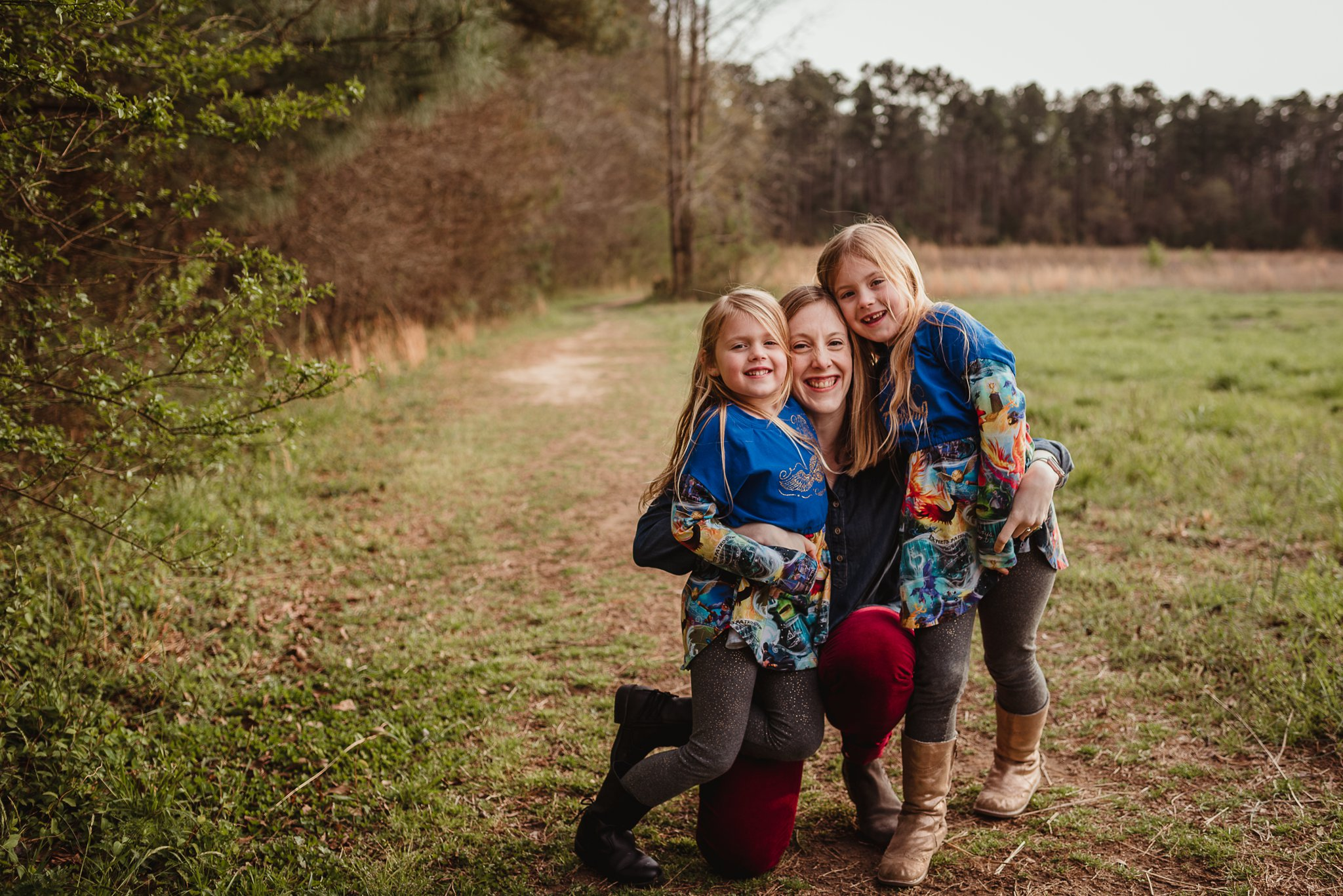 The daughters sit close with their mom during their family photo session with Rose Trail Images in Wake Forest, North Carolina.