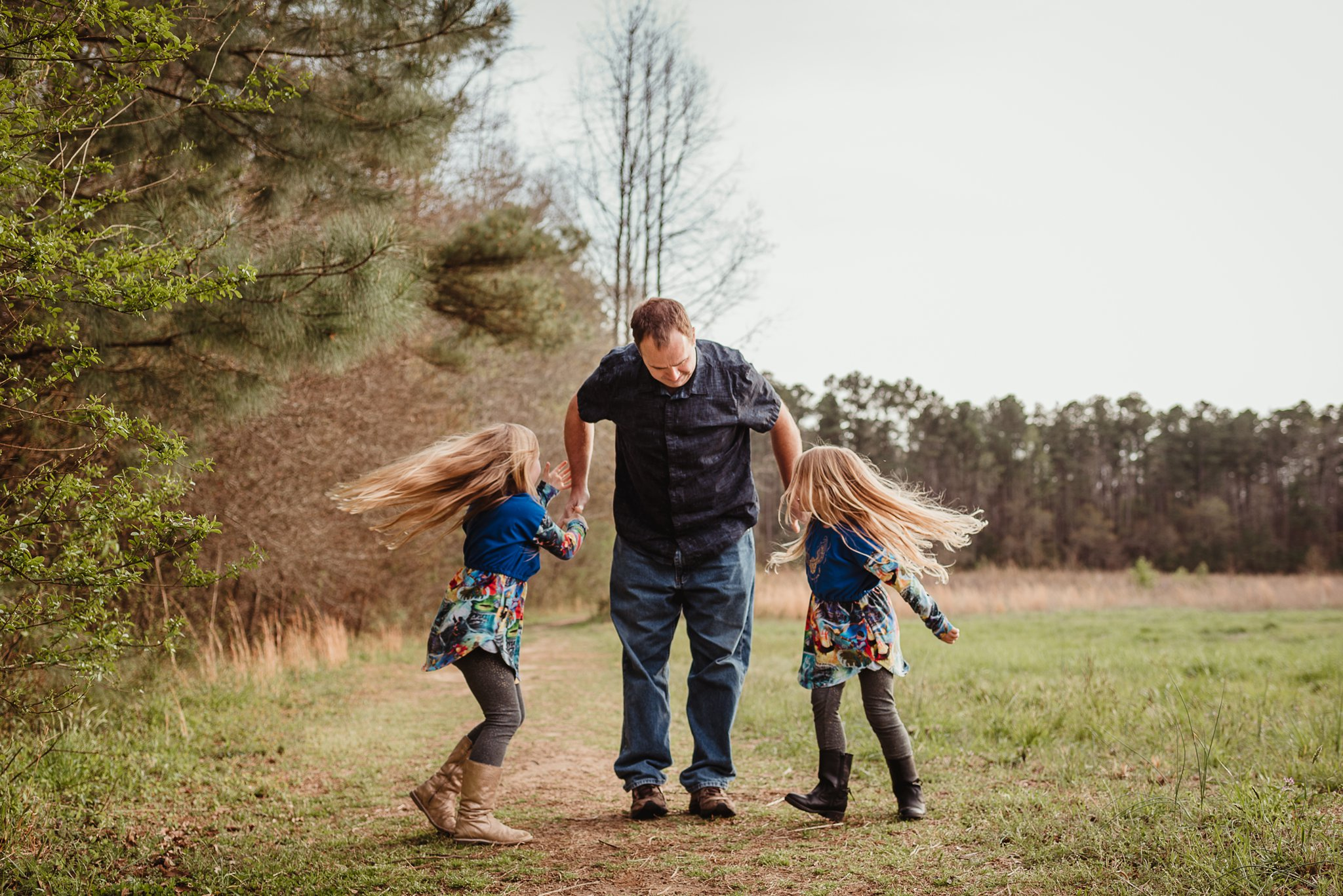 The daughters dance with their dad during their family photo session with Rose Trail Images in Wake Forest, North Carolina.