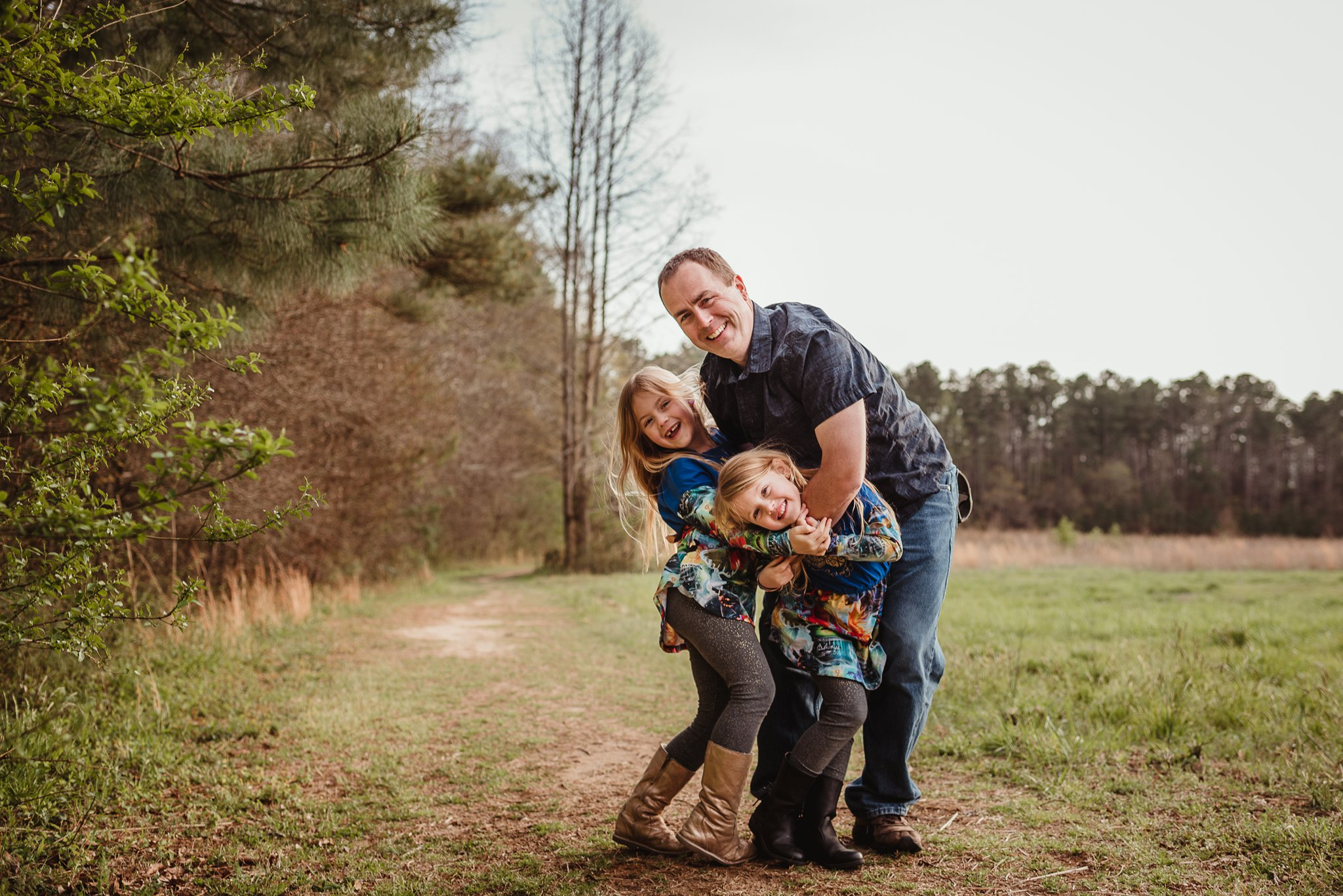 The daughters snuggle with their dad during their family photo session with Rose Trail Images in Wake Forest, North Carolina.
