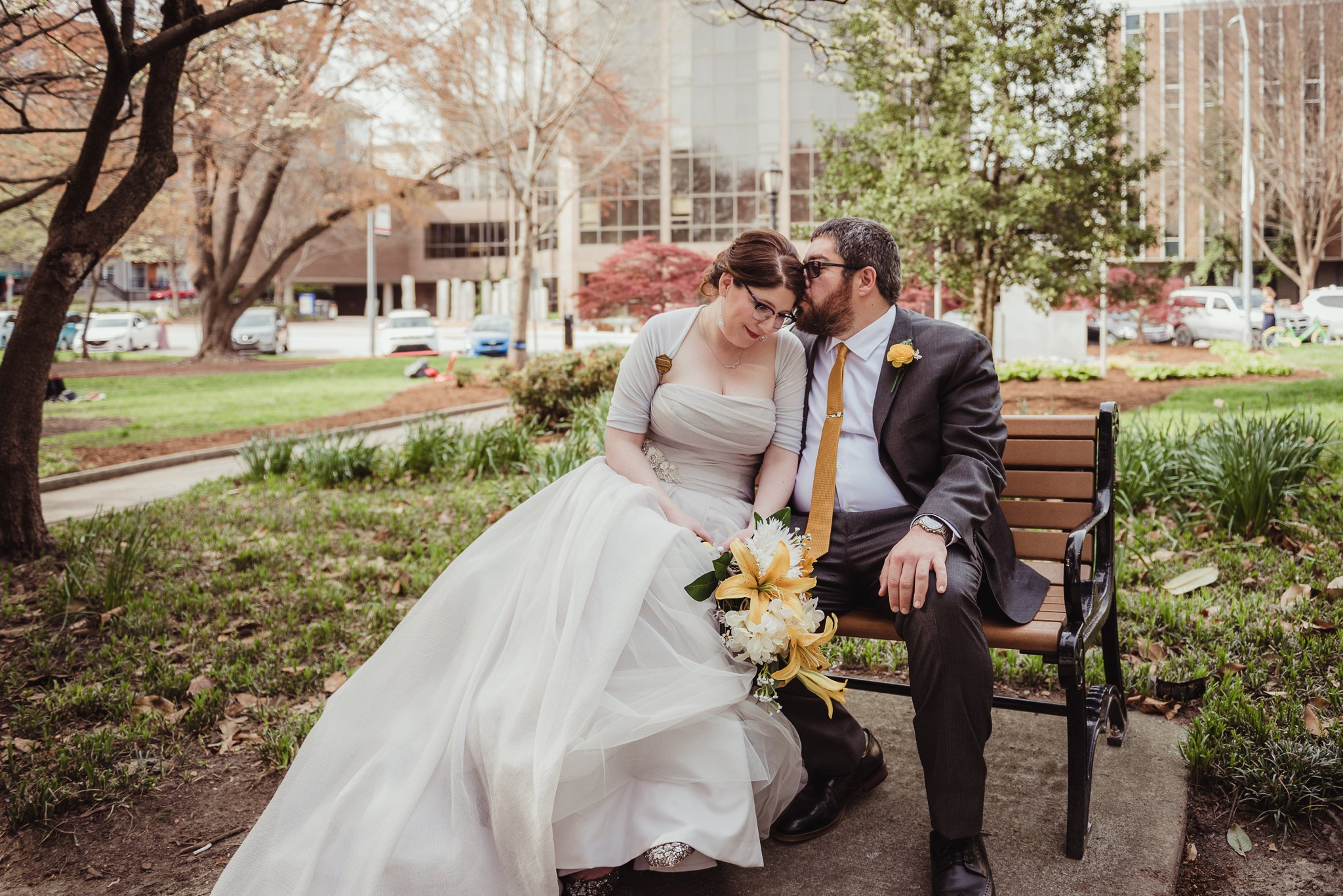 The bride and groom sit together in the park before their wedding day in downtown Raleigh, picture by Rose Trail Images.