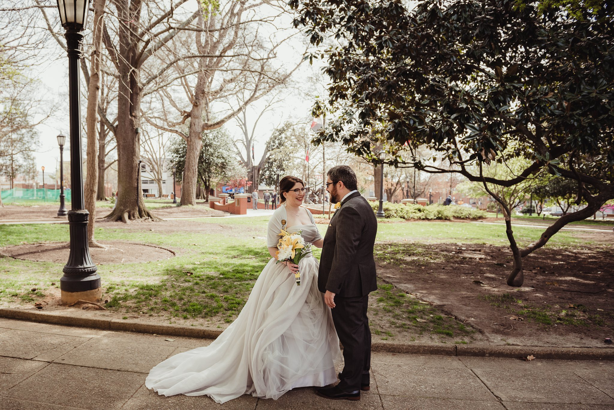 The bride and groom laugh together in the park before their wedding day in downtown Raleigh, picture by Rose Trail Images.
