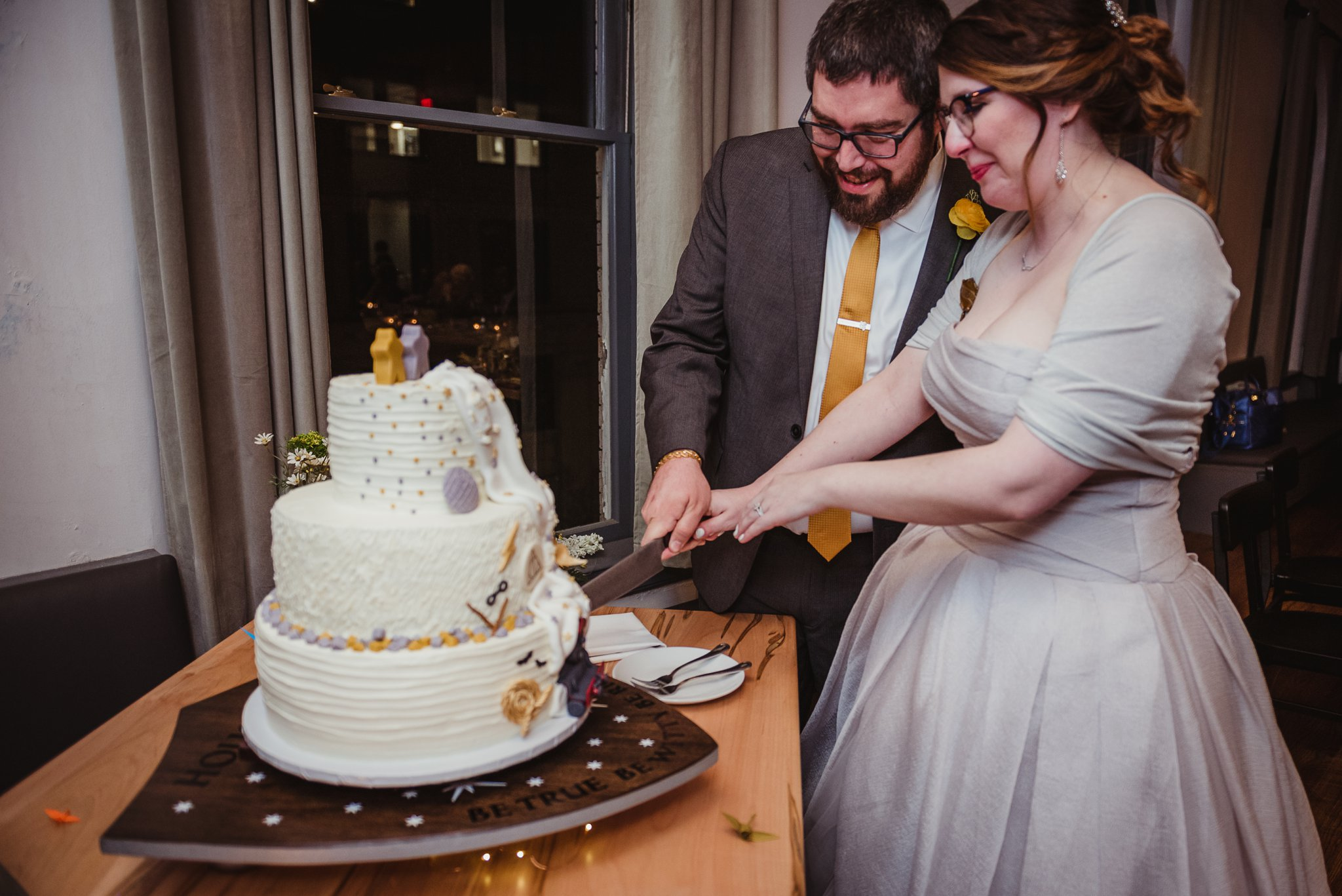The bride and groom cut their Harry Potter/Star Wars/Lord of the Rings wedding cake at their wedding reception in Raleigh, NC, picture by Rose Trail Images.