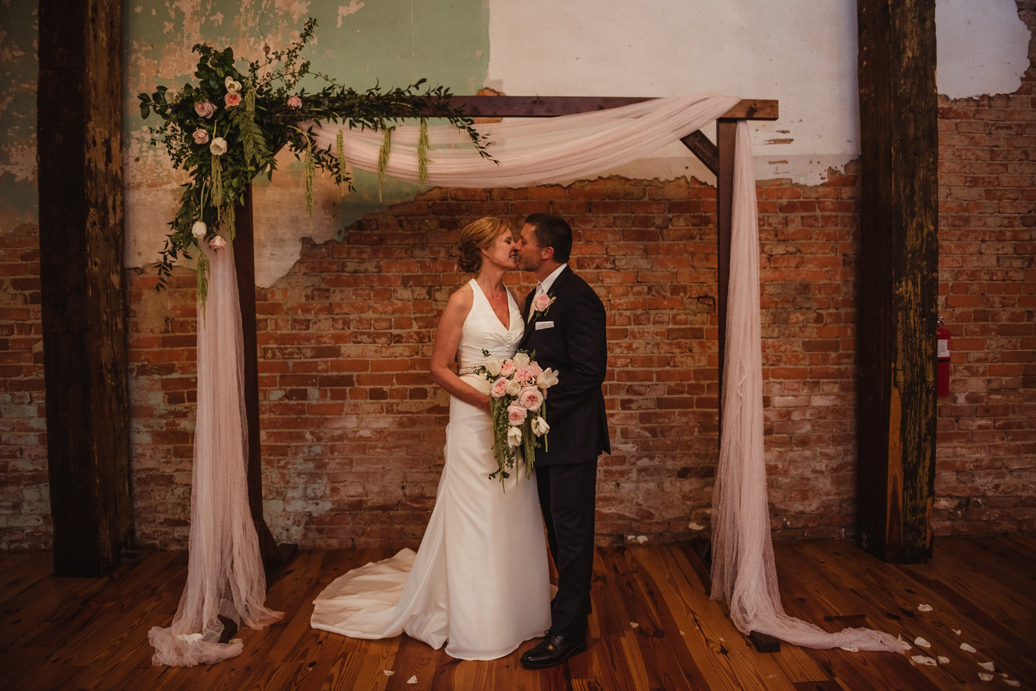 The bride and groom stand together underneath the homemade archway after their wedding at Cross and Main, image by Rose Trail Images.