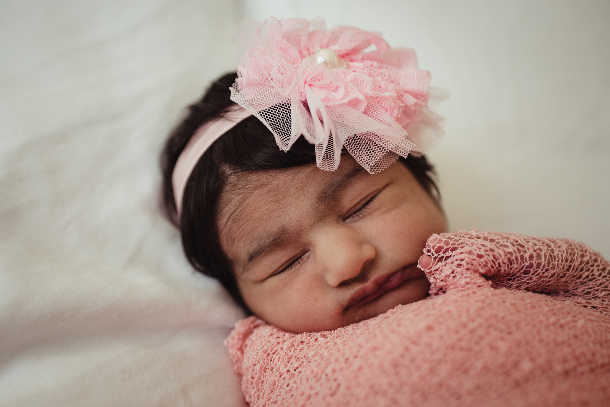 The newborn baby girl sleeps on her parents' bed during her lifestyle newborn session with Rose Trail Images in Raleigh, North Carolina.