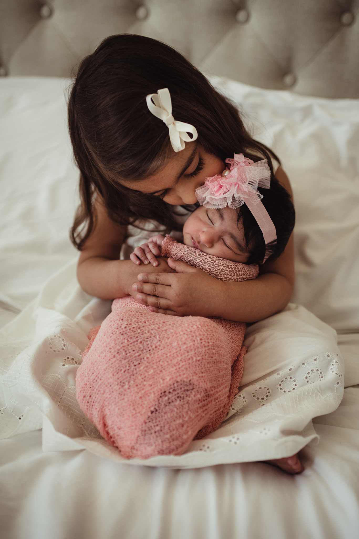 Older sister kisses her new baby sister during their lifestyle newborn session with Rose Trail Images in Raleigh, North Carolina.