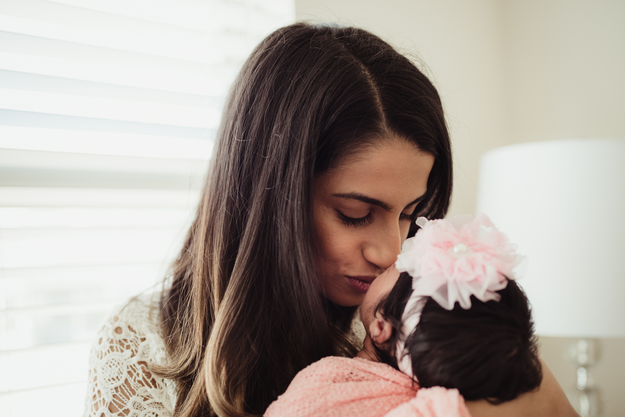 Mom kisses her newborn girl during their lifestyle newborn session with Rose Trail Images in Raleigh, North Carolina.