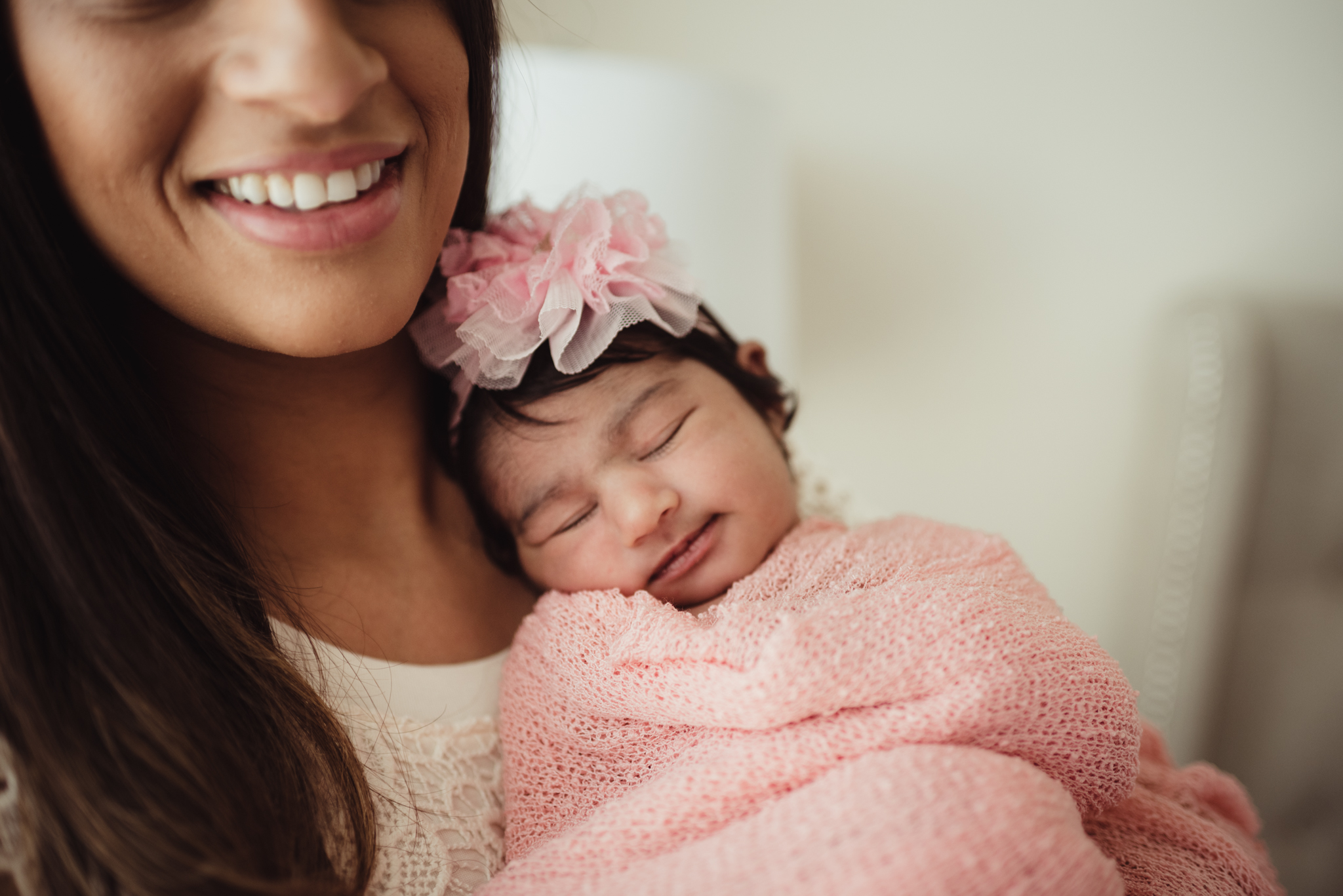 Mom poses with her smiley newborn girl during their lifestyle newborn session with Rose Trail Images in Raleigh, North Carolina.
